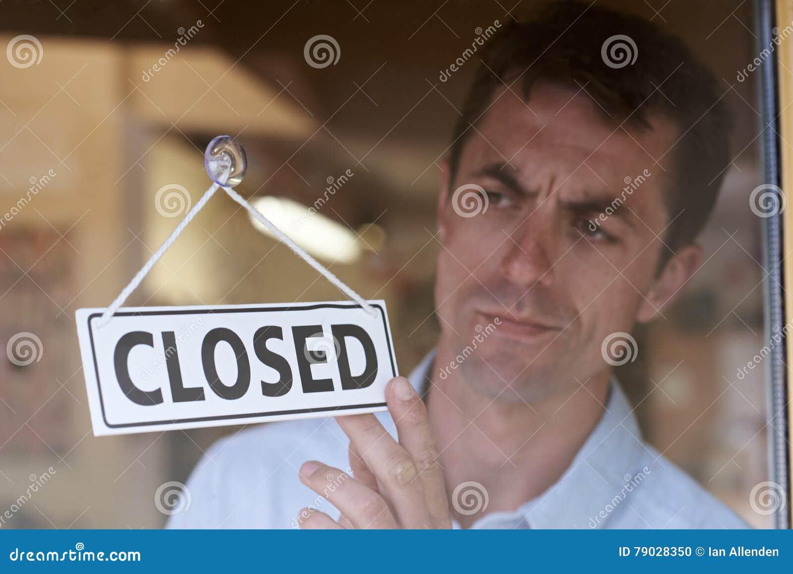 Ιδιοκτήτης καταστημάτων που γυρίζει το κλειστό σημάδι στην πόρτα καταστημάτων