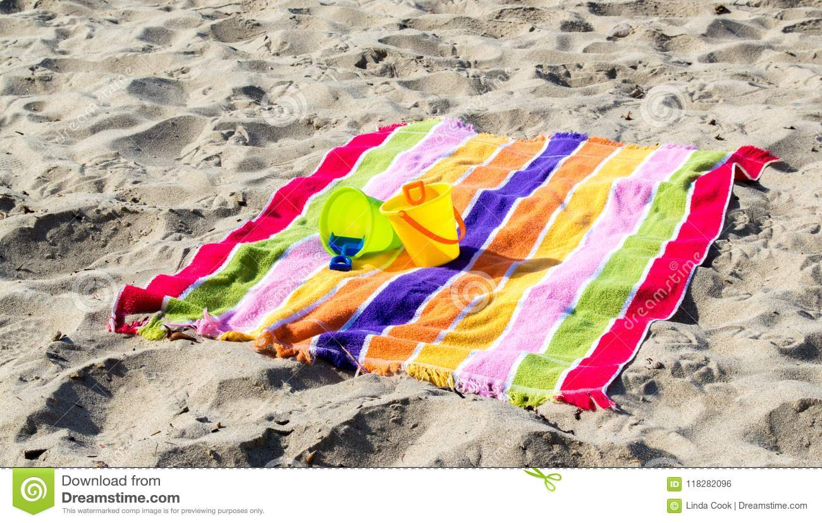 2 κάδοι και φτυάρια άμμου παιδιών ` s σε μια ριγωτή πετσέτα παραλιών