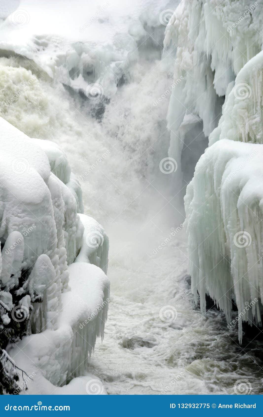 Κάθετη φωτογραφία των μικρών καταρρακτών που πέφτουν απότομα στο στενό ποταμό με τις τράπεζες που καλύπτονται στο χιόνι και το πα