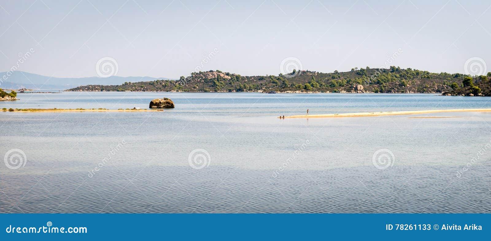 Κάνοντας ηλιοθεραπεία στην παραλία σε Halkidiki, Ελλάδα