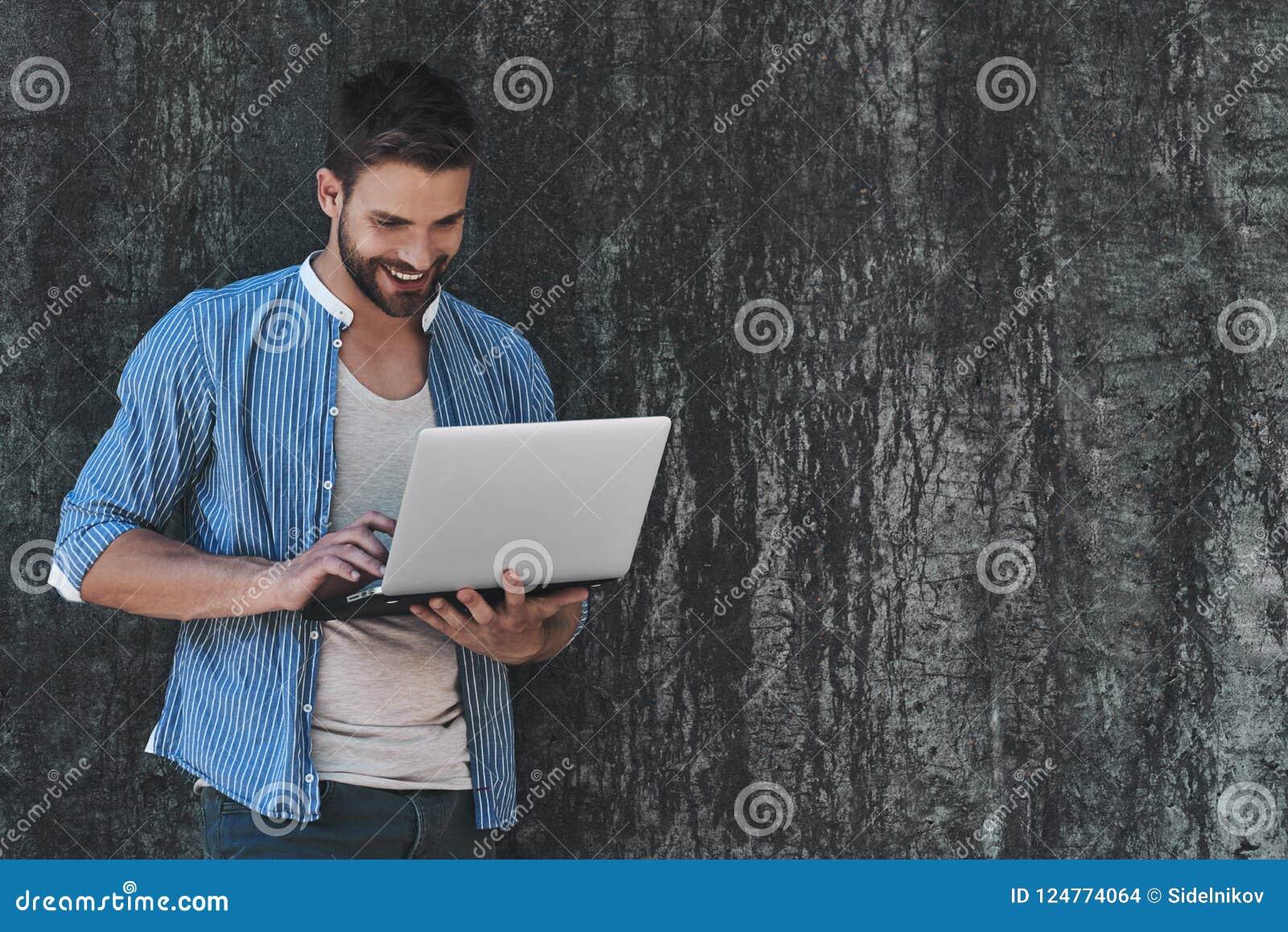 Κάνοντας σερφ τον καθαρό υπαίθρια Όμορφος νεαρός άνδρας στην έξυπνη περιστασιακή ένδυση που εργάζεται στο lap-top καθμένος υπαίθρ
