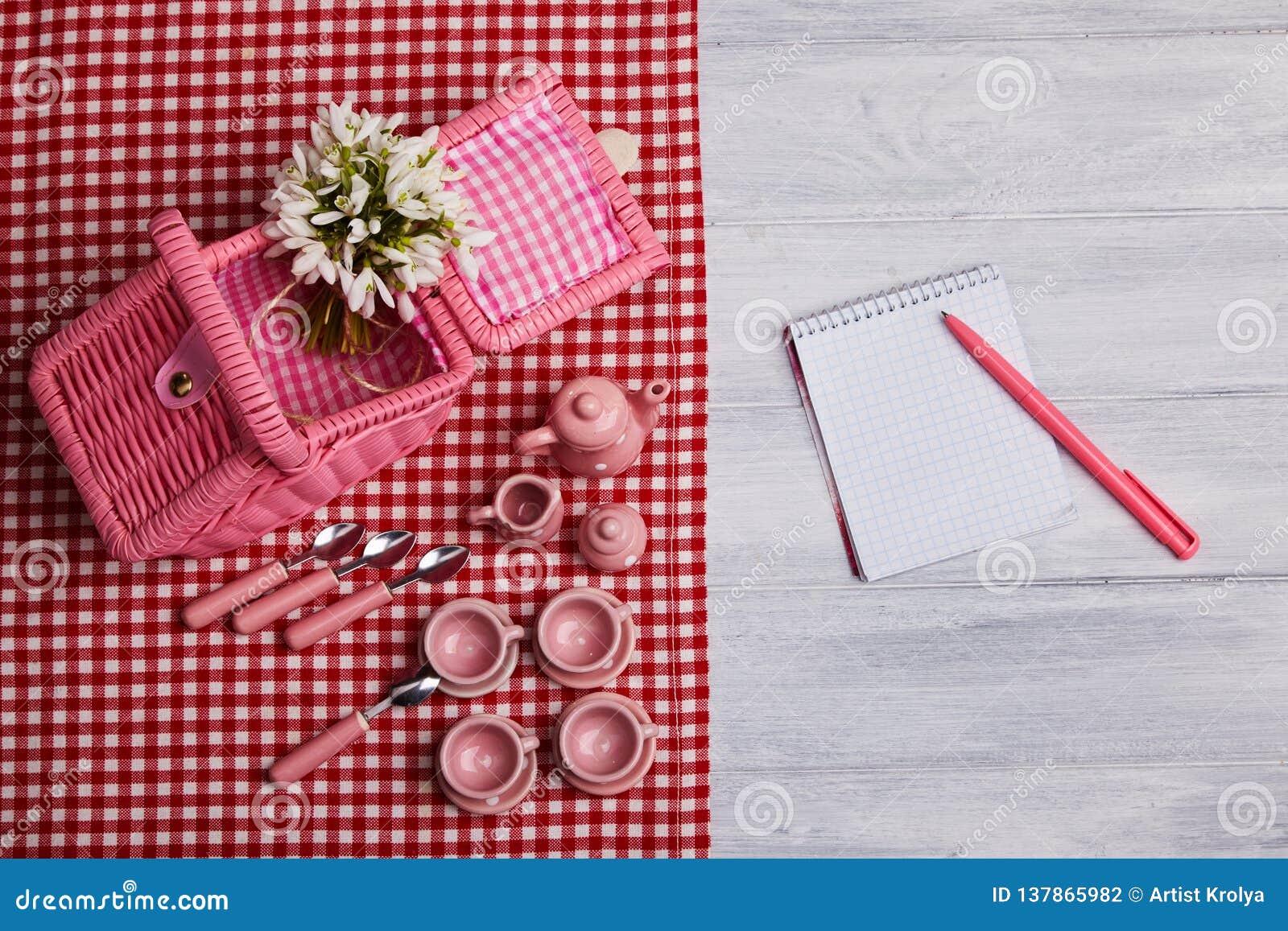 Κάρτα πικ-νίκ με την επιτραπέζια ρύθμιση και snowdrops, τις ασημικές, κόκκινη άσπρη ελεγχμένη πετσέτα