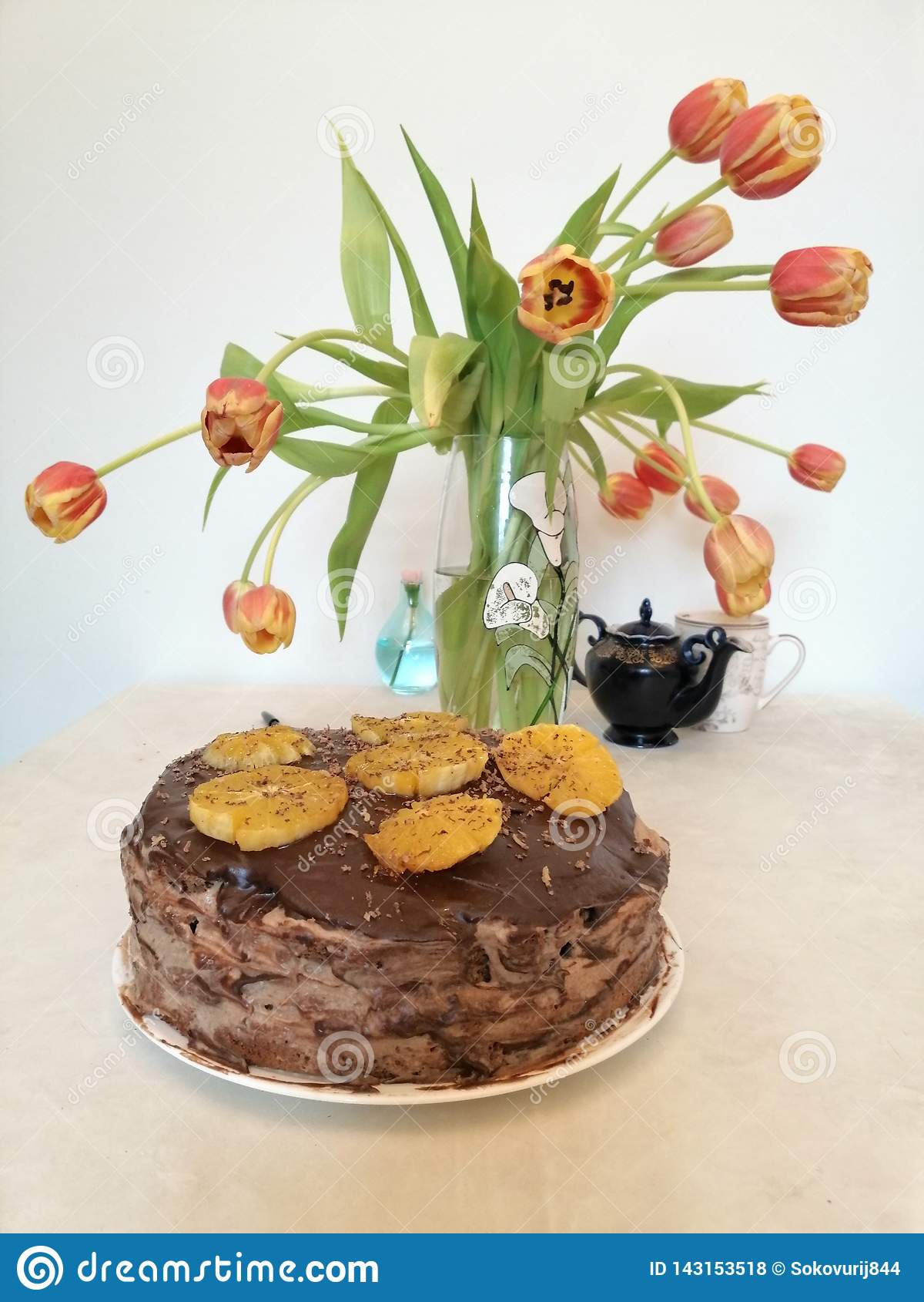 Κέικ σοκολάτας που διακοσμείται με τα πορτοκάλια στο υπόβαθρο των τουλιπών