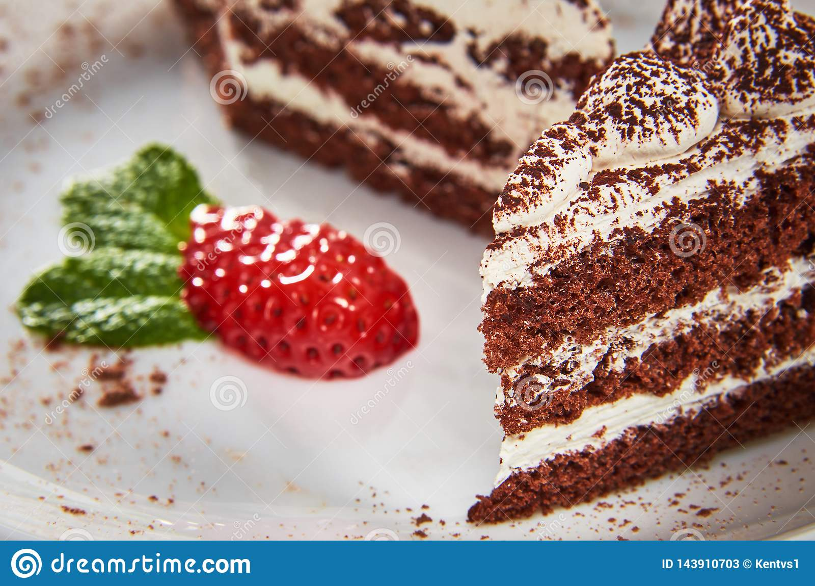Κέικ σοκολάτας σε ένα άσπρο πιάτο με τις φράουλες και τη μέντα