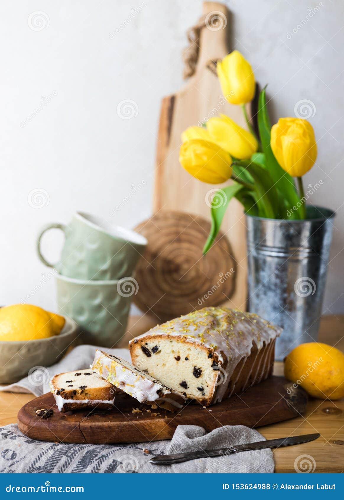 Κέικ σταφίδων σε έναν ξύλινο πίνακα με το λεμόνι και τις κίτρινες τουλίπες