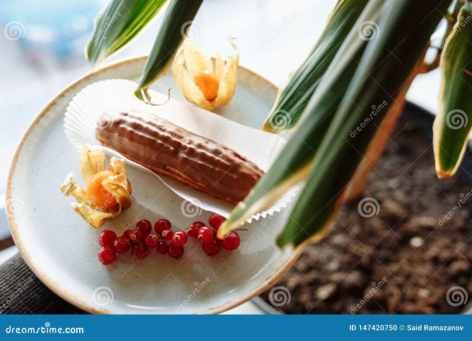Κέικ ECLAIR σε ένα πιάτο που διακοσμούνται με τα εσπεριδοειδή και τα μούρα και τα φύλλα ενός houseplant στο πρώτο πλάνο