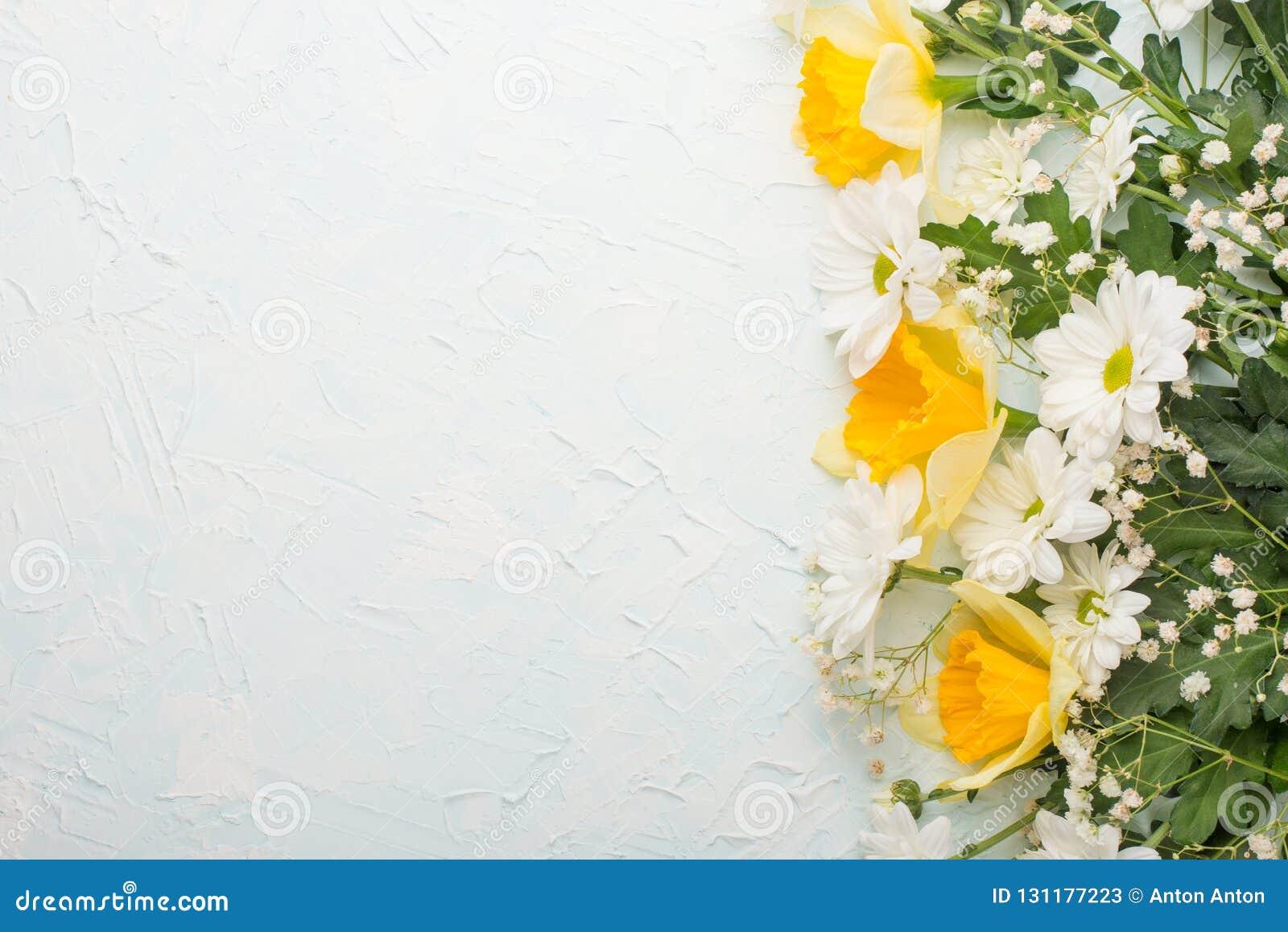 Κίτρινα daffodils με τα άσπρα crisands σε ένα ξύλινο υπόβαθρο, τοπ άποψη, με το κενό διάστημα για το γράψιμο ή τη διαφήμιση