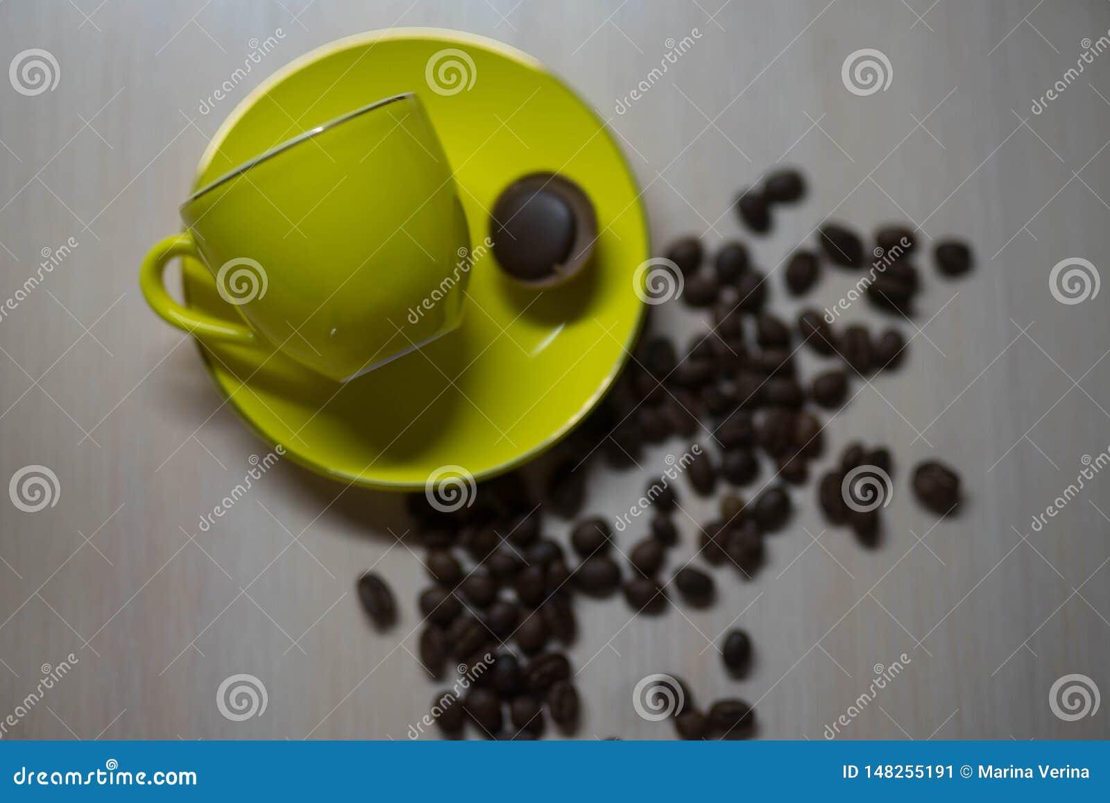 Κίτρινη κούπα με μια φράουλα και τα σιτάρια του καφέ