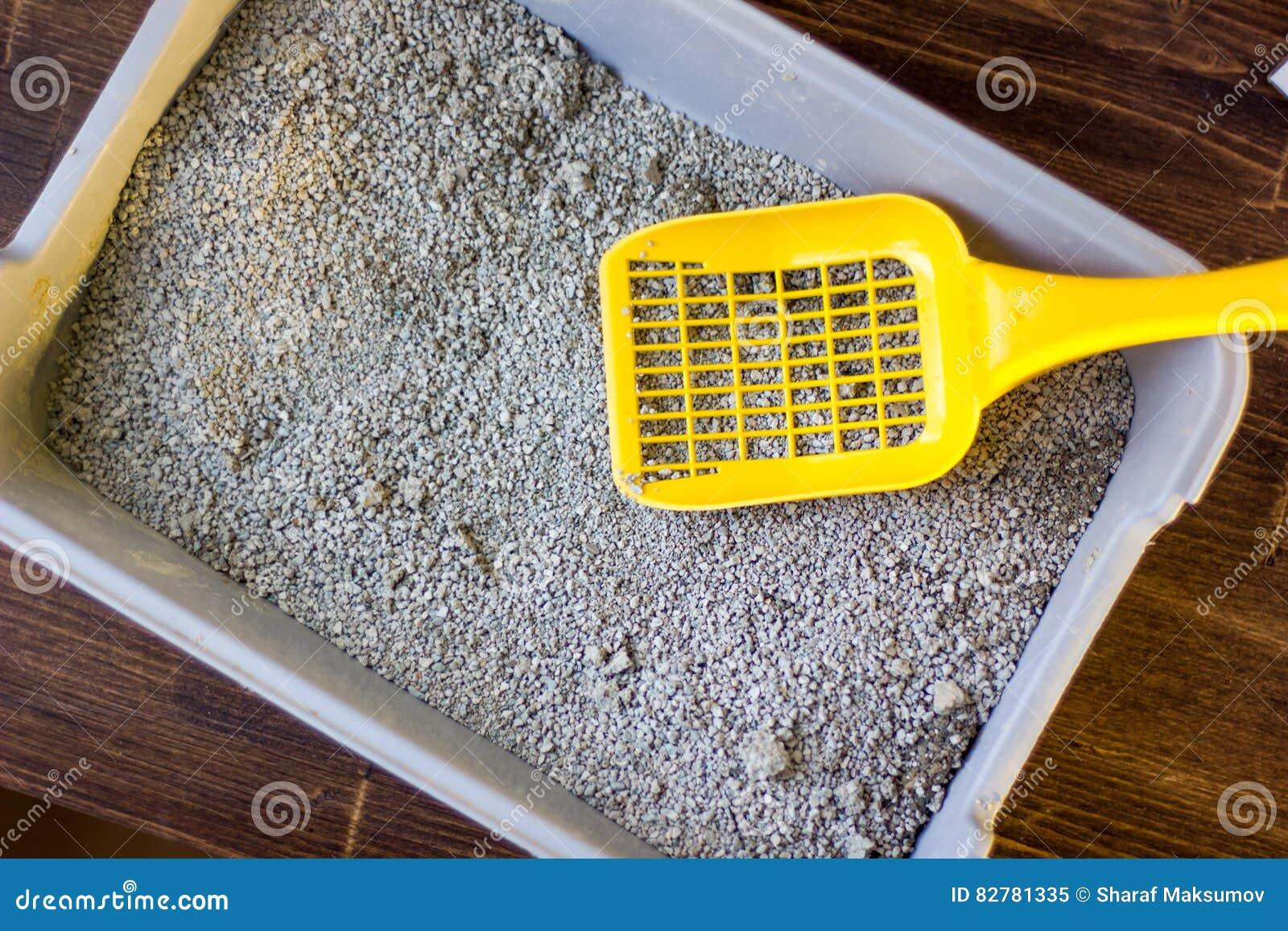 Κίτρινη πλαστική σέσουλα στο γκρίζο πεδίο απορριμάτων, από η μπλε που γεμίζει άμμος απορριμάτων