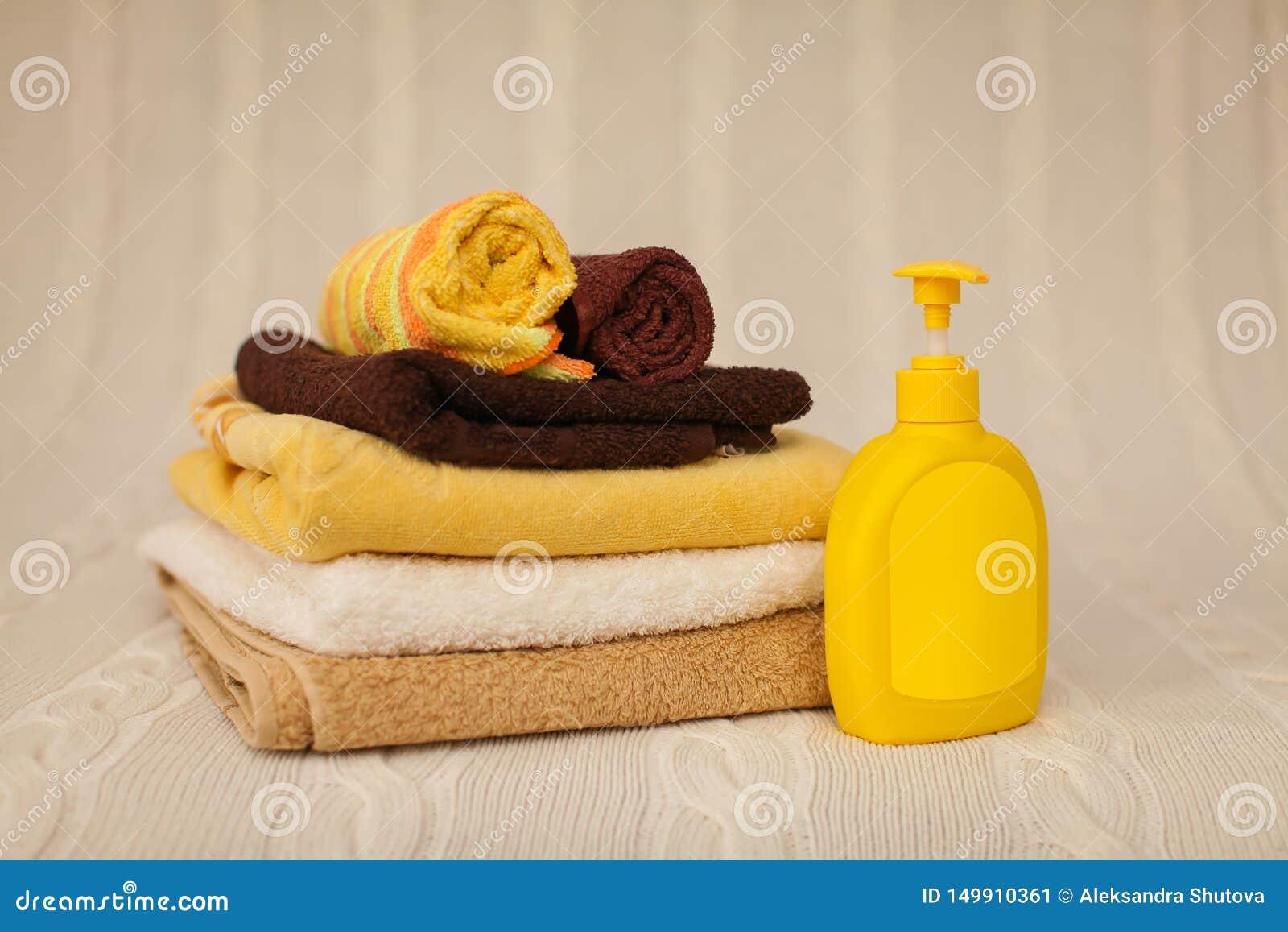 Κίτρινος πλαστικός διανομέας με το υγρό σαπούνι και ένας σωρός των καφετιών πετσετών σε μια μπεζ κουβέρτα στην εκλεκτική εστίαση