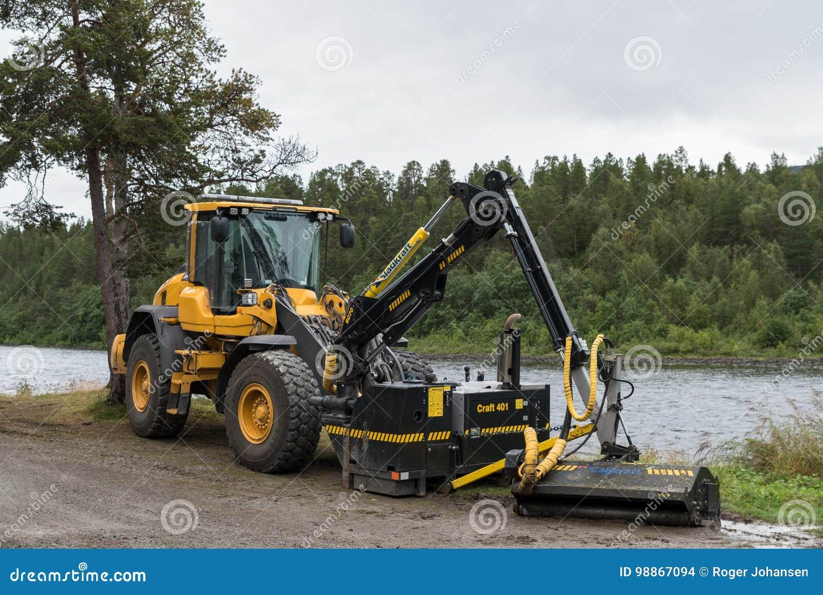 Κίτρινος φορτωτής της VOLVO με τον κόπτη χλόης