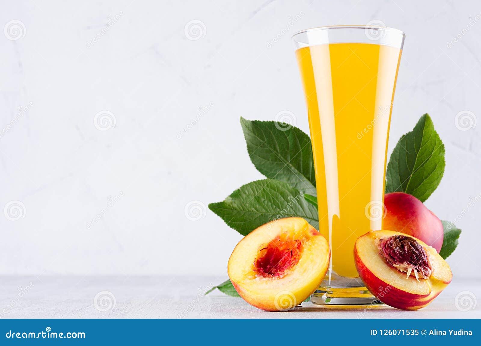 Κίτρινος χυμός στο γυαλί και juicy ώριμα κόκκινα νεκταρίνια με τα πράσινα φύλλα, φέτα, σπόρος στο μαλακό ελαφρύ λευκό ξύλινο πίνα