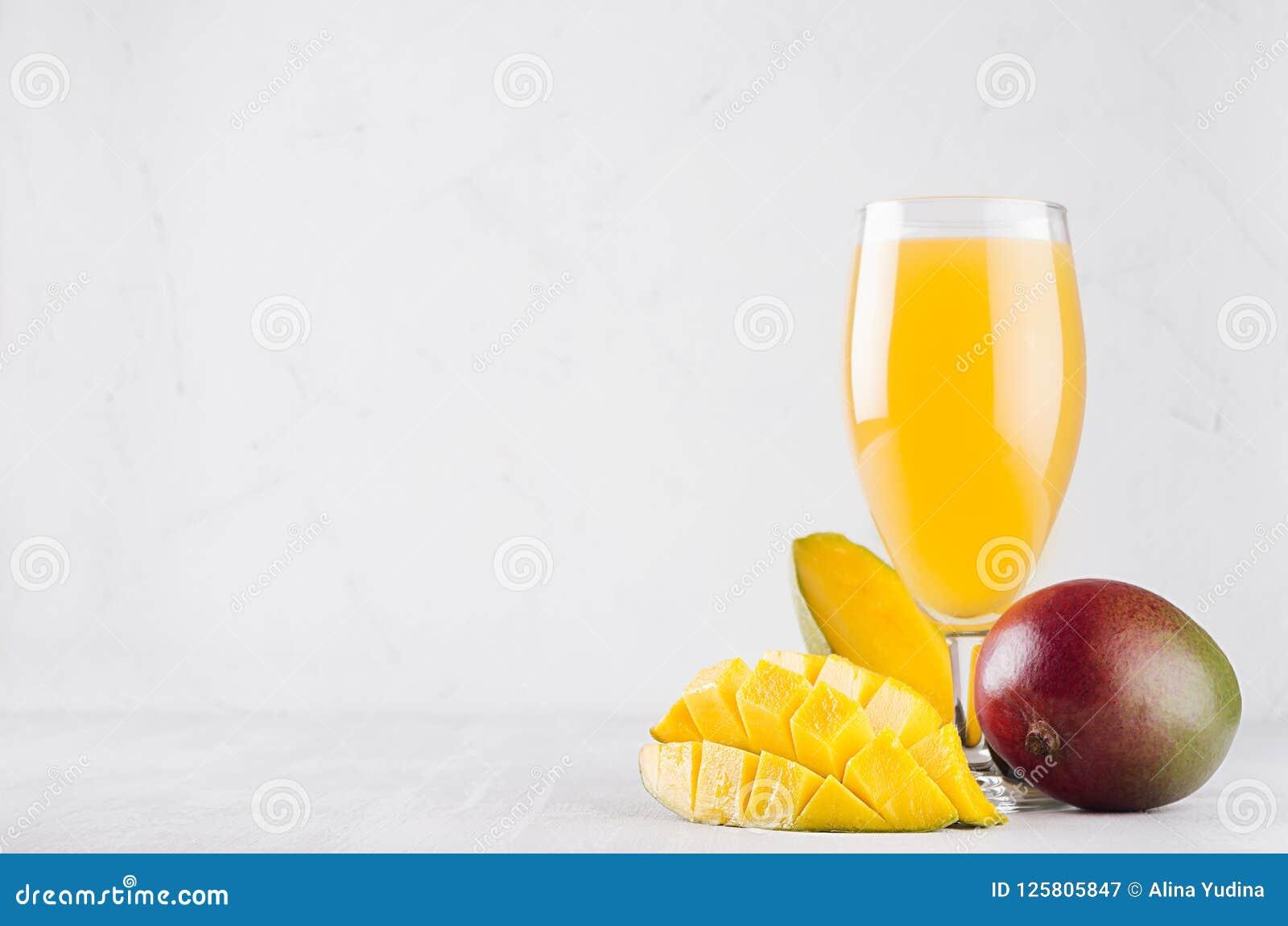 Κίτρινος χυμός στο κομψό γυαλί με το ώριμο μάγκο και τεμαχισμένο μισό στο λευκό ξύλινο πίνακα Εξωτικός χυμός φρούτων