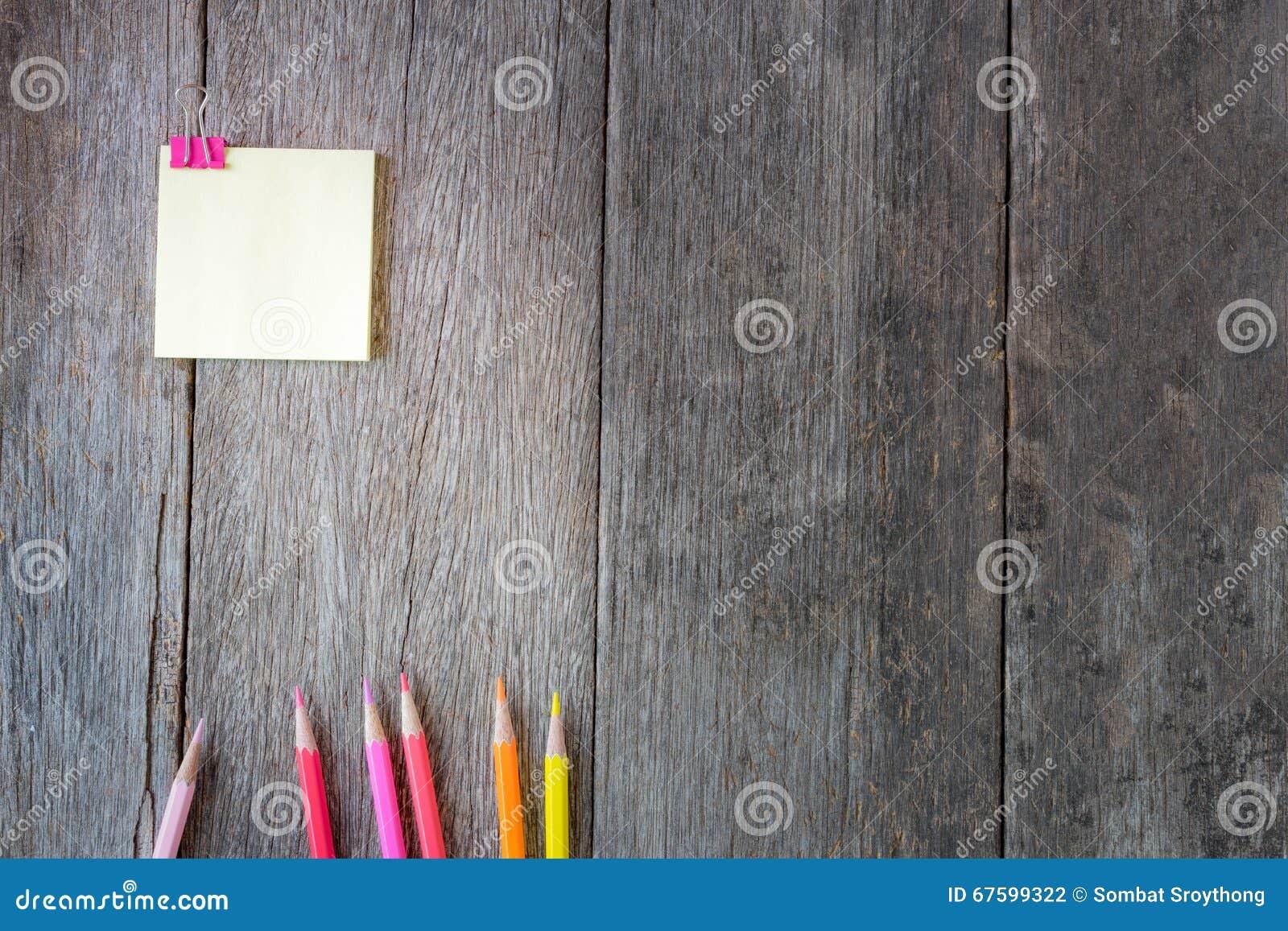 Κίτρινο έγγραφο σημειώσεων για το ξύλινο υπόβαθρο με τα χρωματισμένα μολύβια