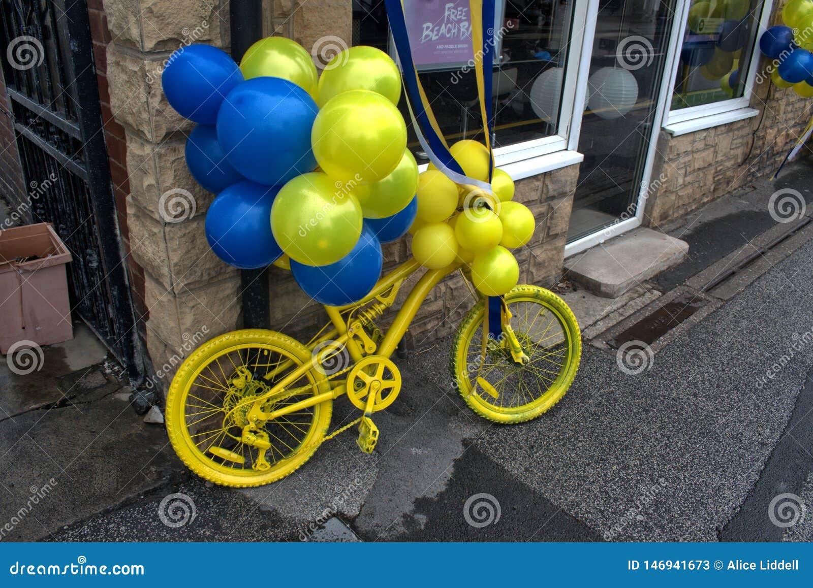 Κίτρινο ποδήλατο, με τα μπλε και κίτρινα μπαλόνια