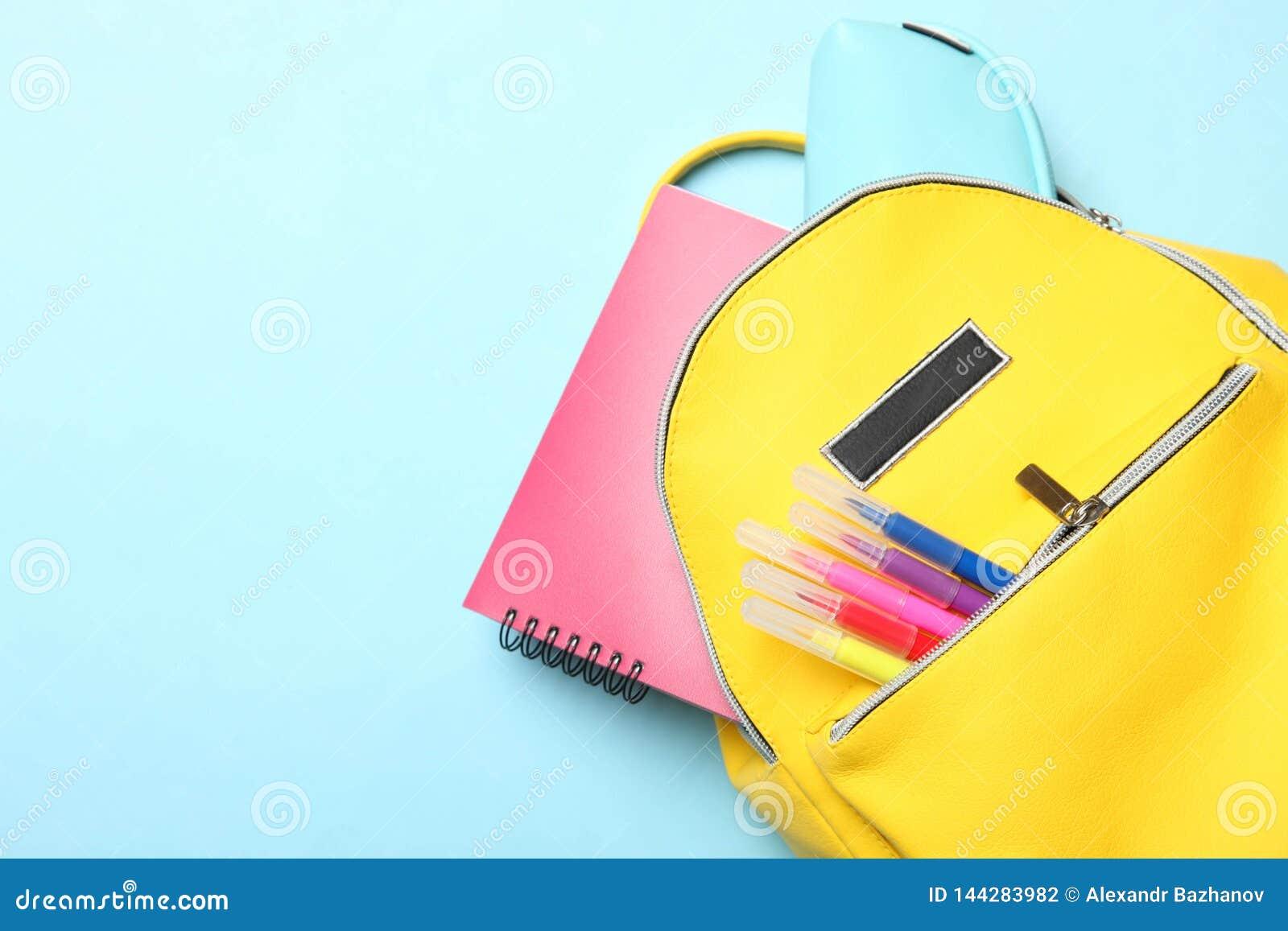 Κίτρινο σακίδιο πλάτης με τις διαφορετικές σχολικές προμήθειες