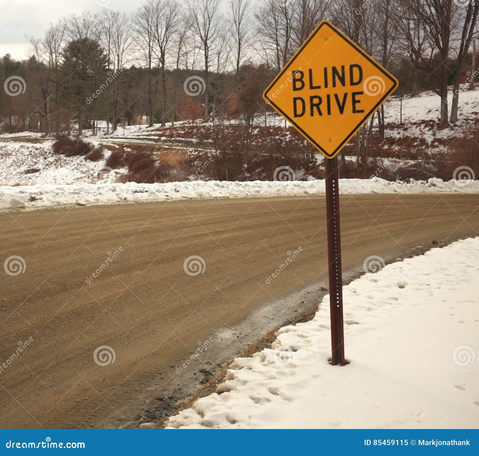 Κίτρινο τυφλό σημάδι κίνησης σε έναν άνεμος βρώμικο δρόμο