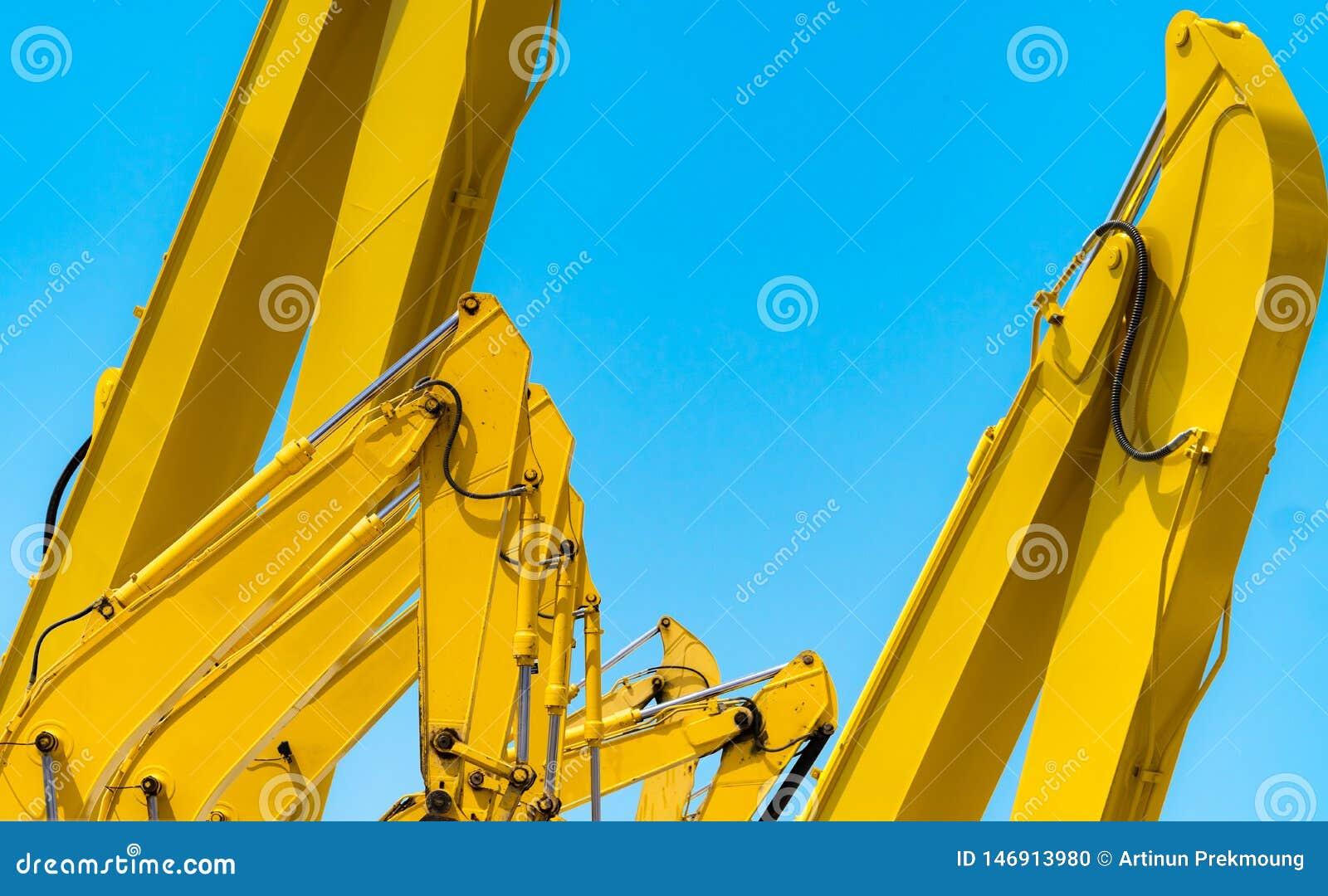 Κίτρινο backhoe με τον υδραυλικό βραχίονα εμβόλων ενάντια στο σαφή μπλε ουρανό Βαριά μηχανή για την ανασκαφή στο εργοτάξιο οικοδο