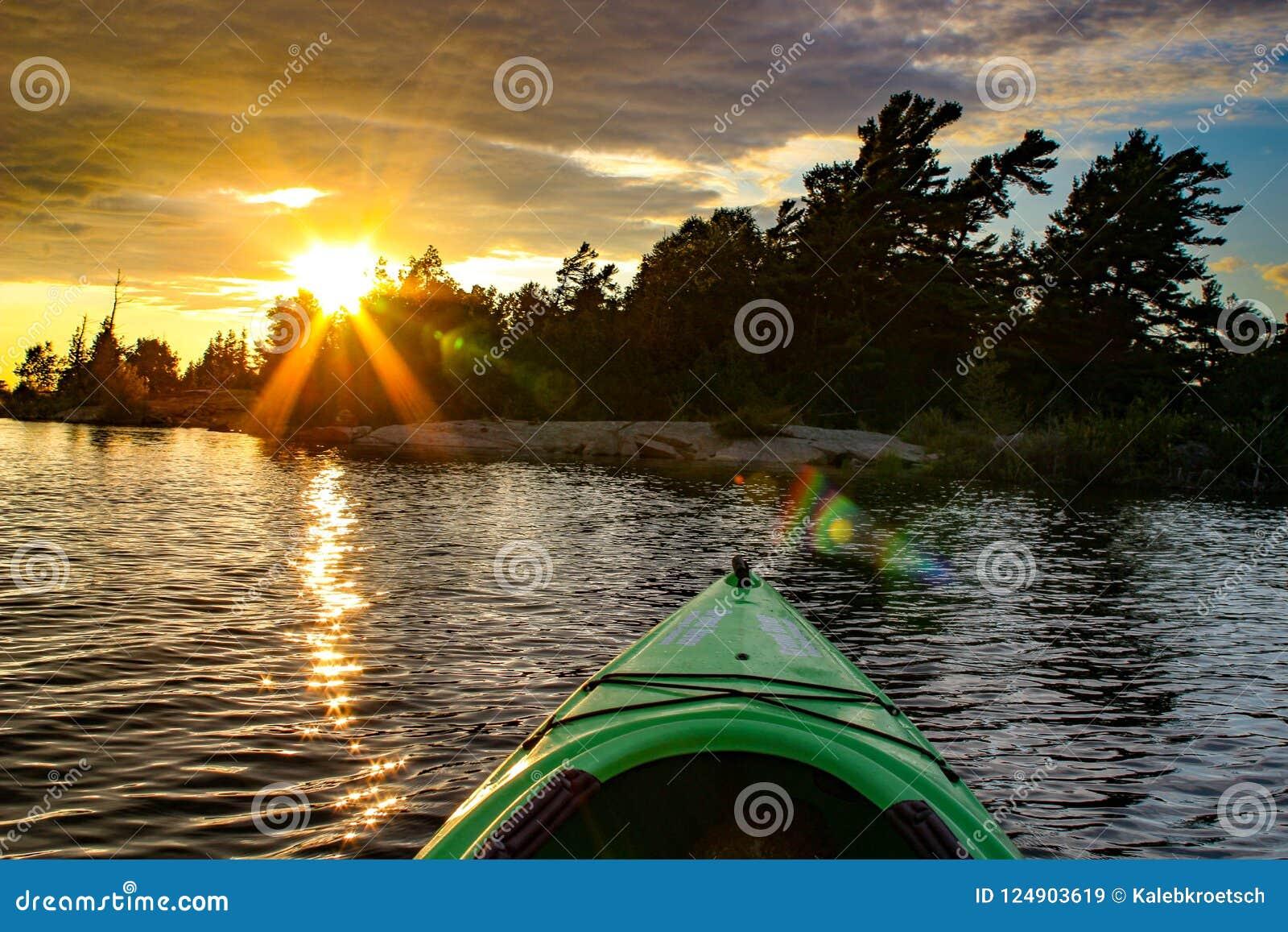 Καγιάκ σε μια λίμνη σε ένα φλογερό ηλιοβασίλεμα Περιοχή του Οντάριο Muskoka