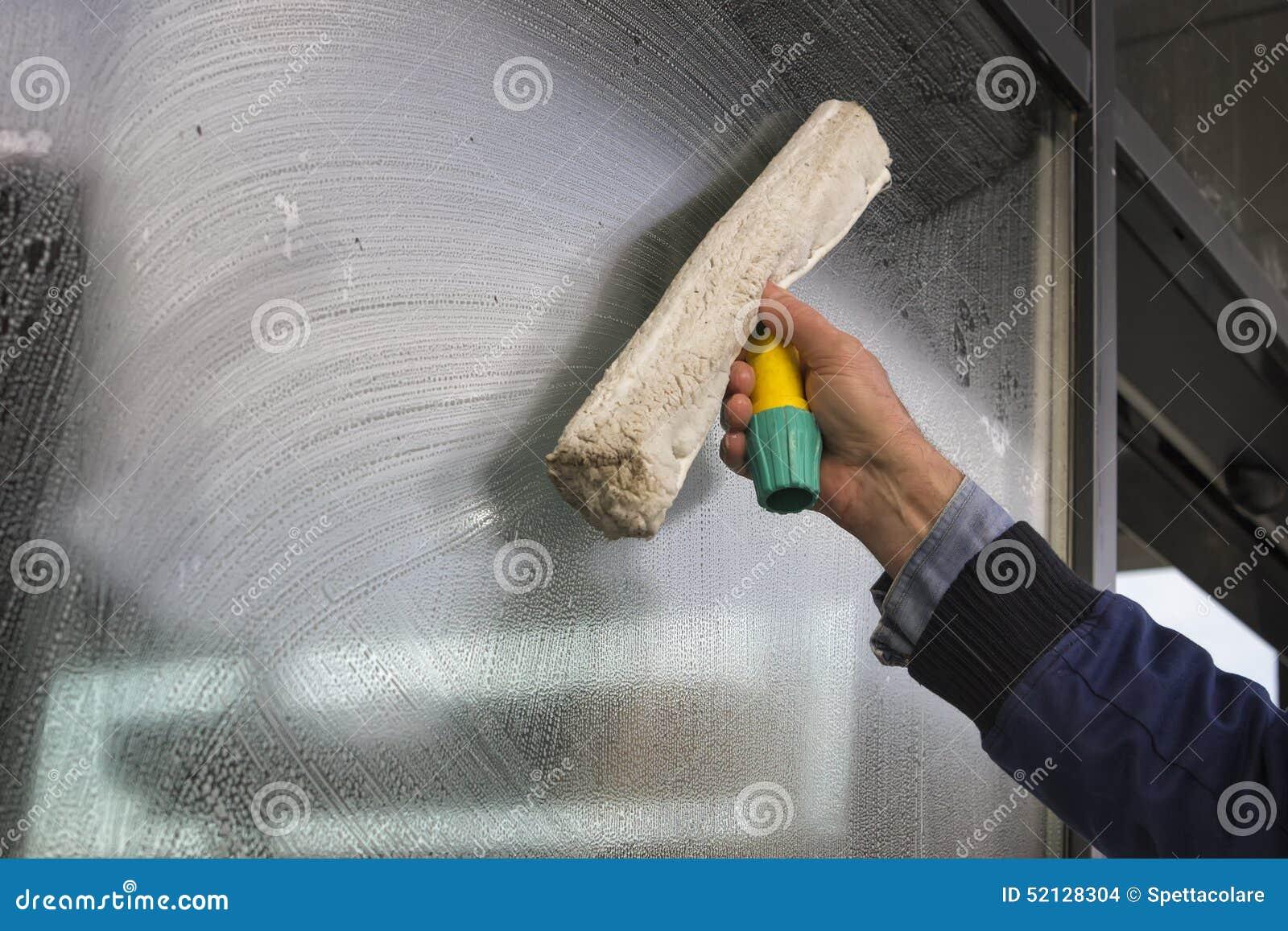 Καθαρίζοντας παράθυρο χεριών ενός κτηρίου