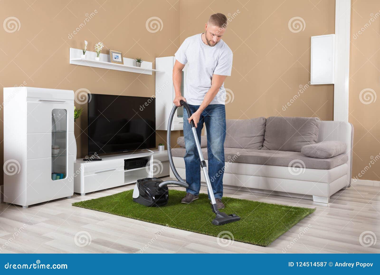 Καθαρίζοντας τάπητας ατόμων με την ηλεκτρική σκούπα