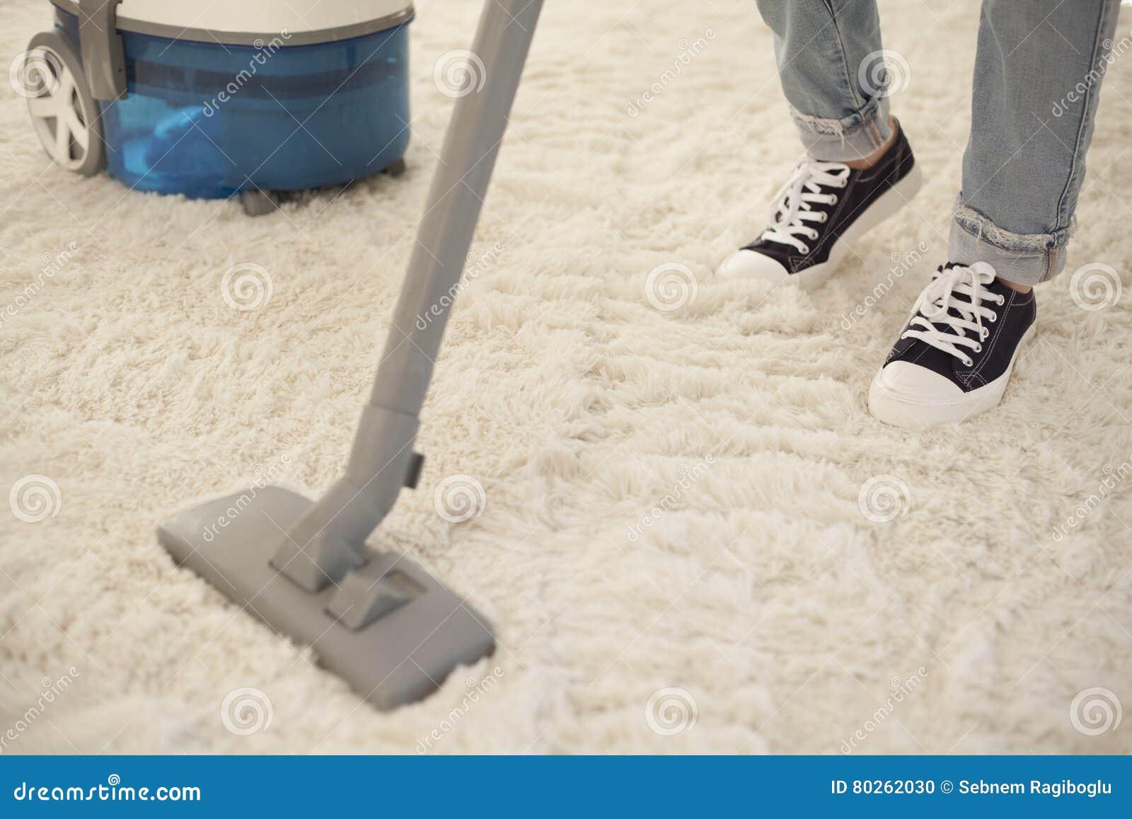 Καθαρίζοντας τάπητας γυναικών με μια ηλεκτρική σκούπα στο δωμάτιο