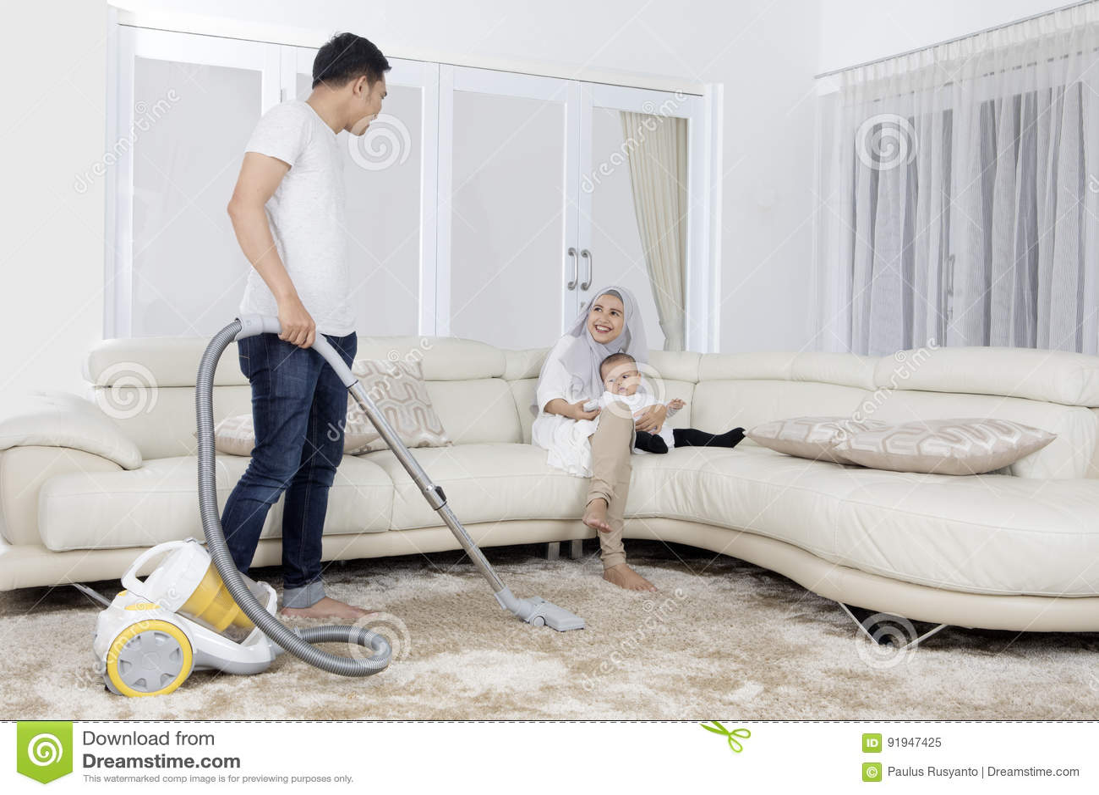 Καθαρίζοντας τάπητας νεαρών άνδρων με την ηλεκτρική σκούπα