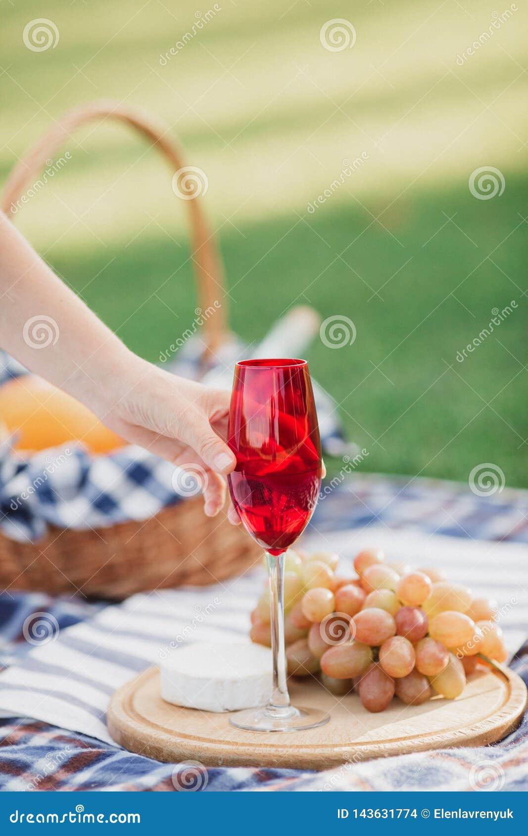 Καλάθι πικ-νίκ με τα ποτά, τα τρόφιμα και τα φρούτα στην πράσινη χλόη έξω στο θερινό πάρκο