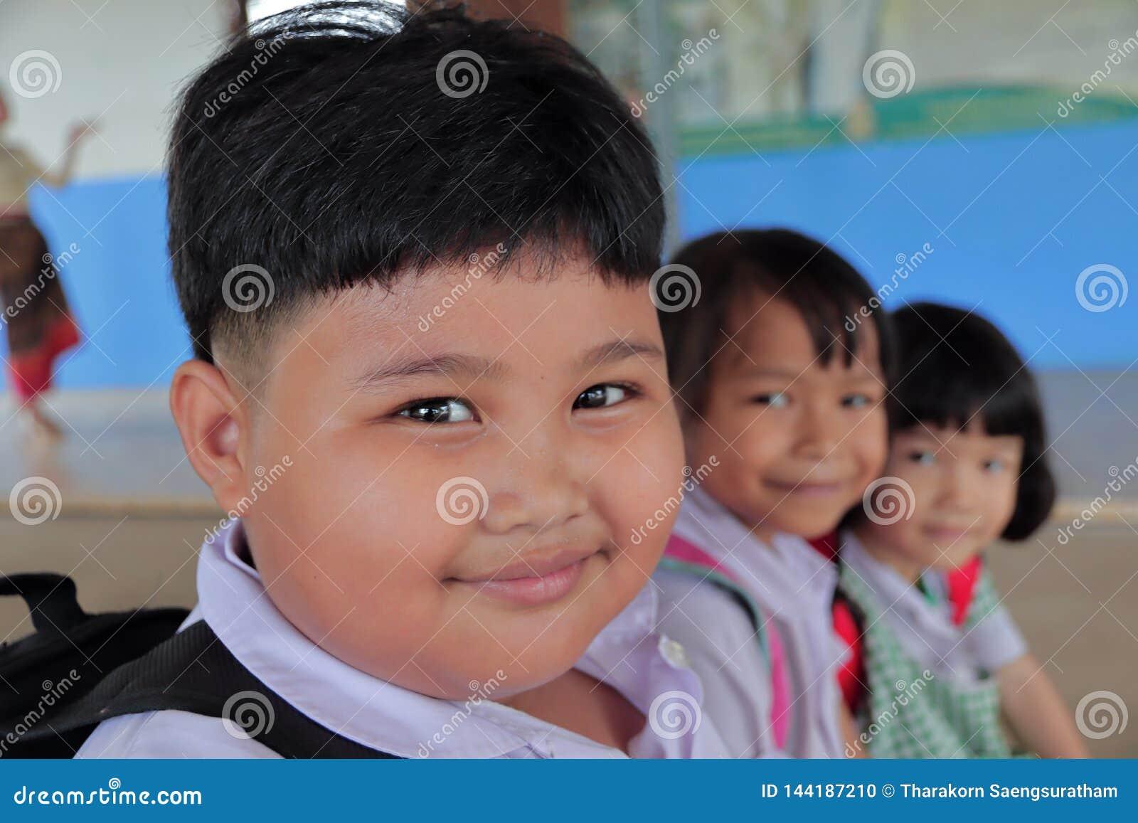 Καλά παχιά κορίτσια στην αγροτική περιοχή που φορούν τη σχολική στολή, σχολική τσάντα Καθίστε στην ξύλινη καρέκλα και το χαμόγελο