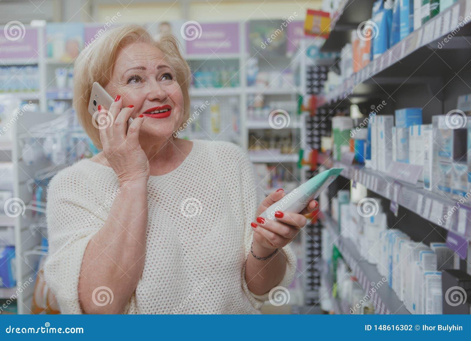 Καλή ανώτερη γυναίκα που ψωνίζει στο φαρμακείο
