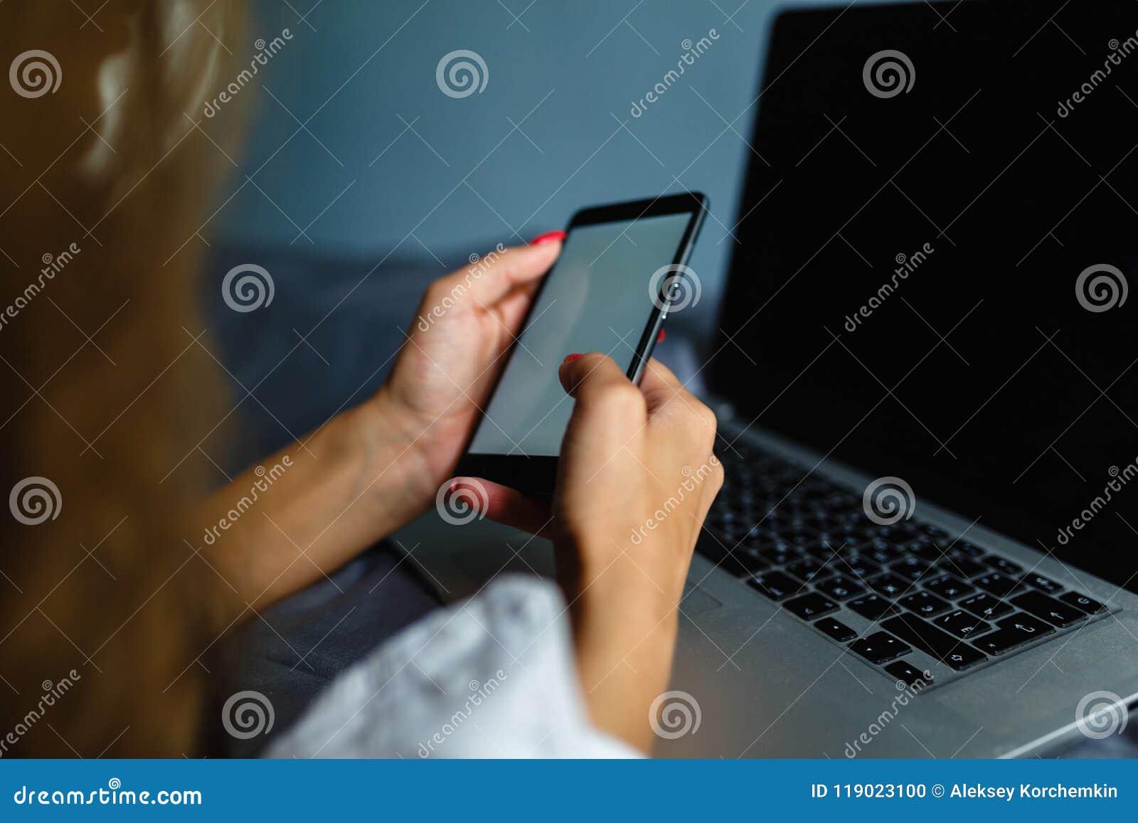Καλή ξανθή γυναίκα που τηλεφωνά με το smartphone της που βρίσκεται στο κρεβάτι της δίπλα στο σημειωματάριό της Κορίτσι που βρίσκε