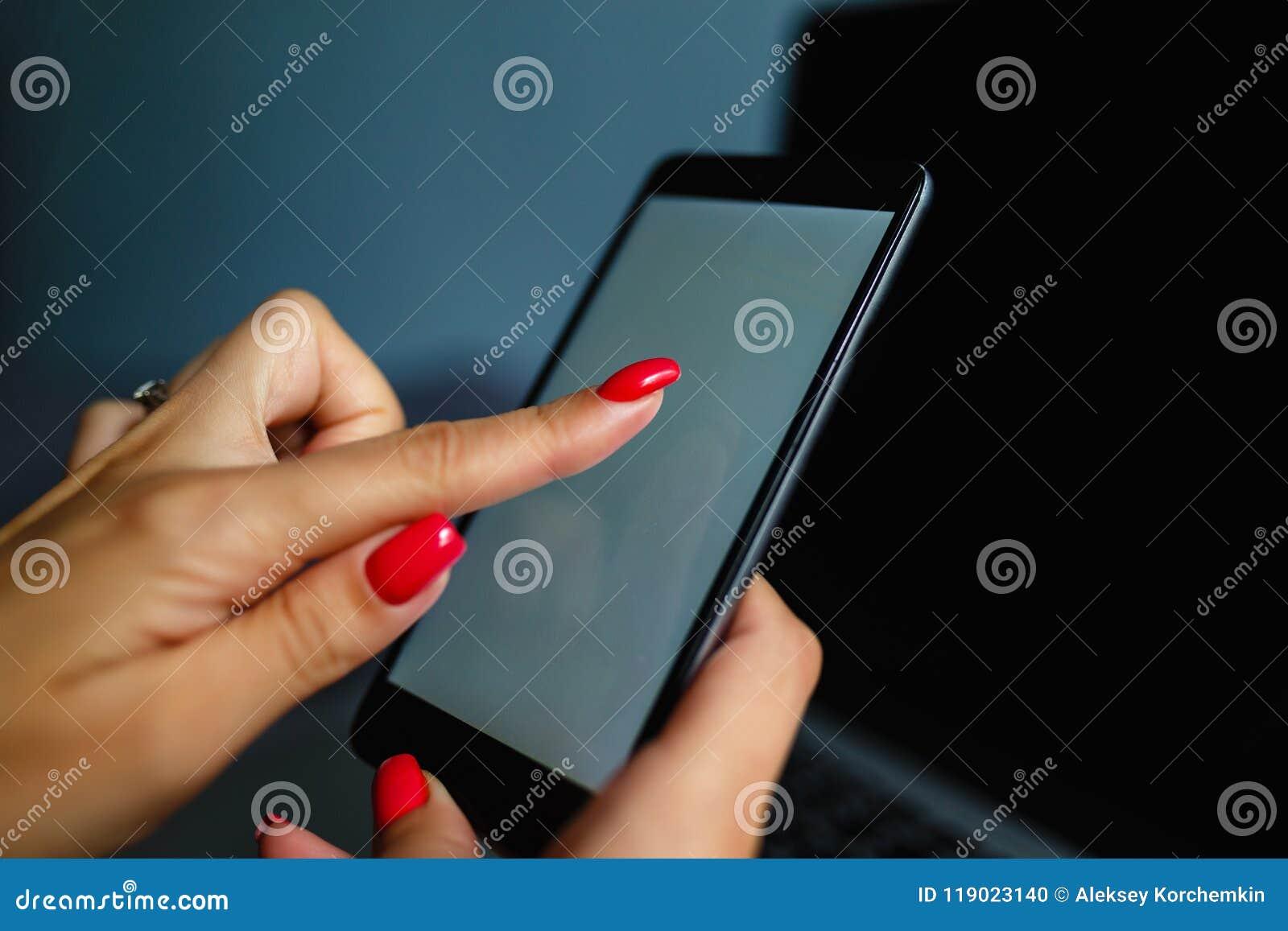 Καλή ξανθή γυναίκα που τηλεφωνά με το smartphone της που βρίσκεται στο κρεβάτι της δίπλα στο σημειωματάριό της Κινητό τηλέφωνο με