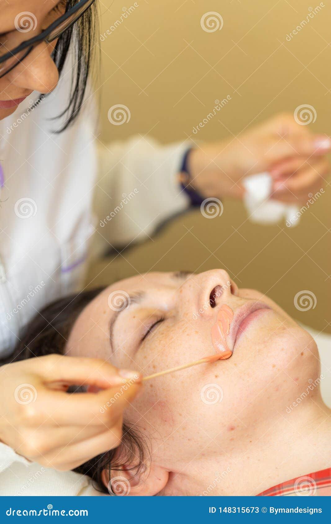 Καλλυντικό που εφαρμόζει το κήρωμα Cosmetician που εφαρμόζει το κερί για το κήρωμα