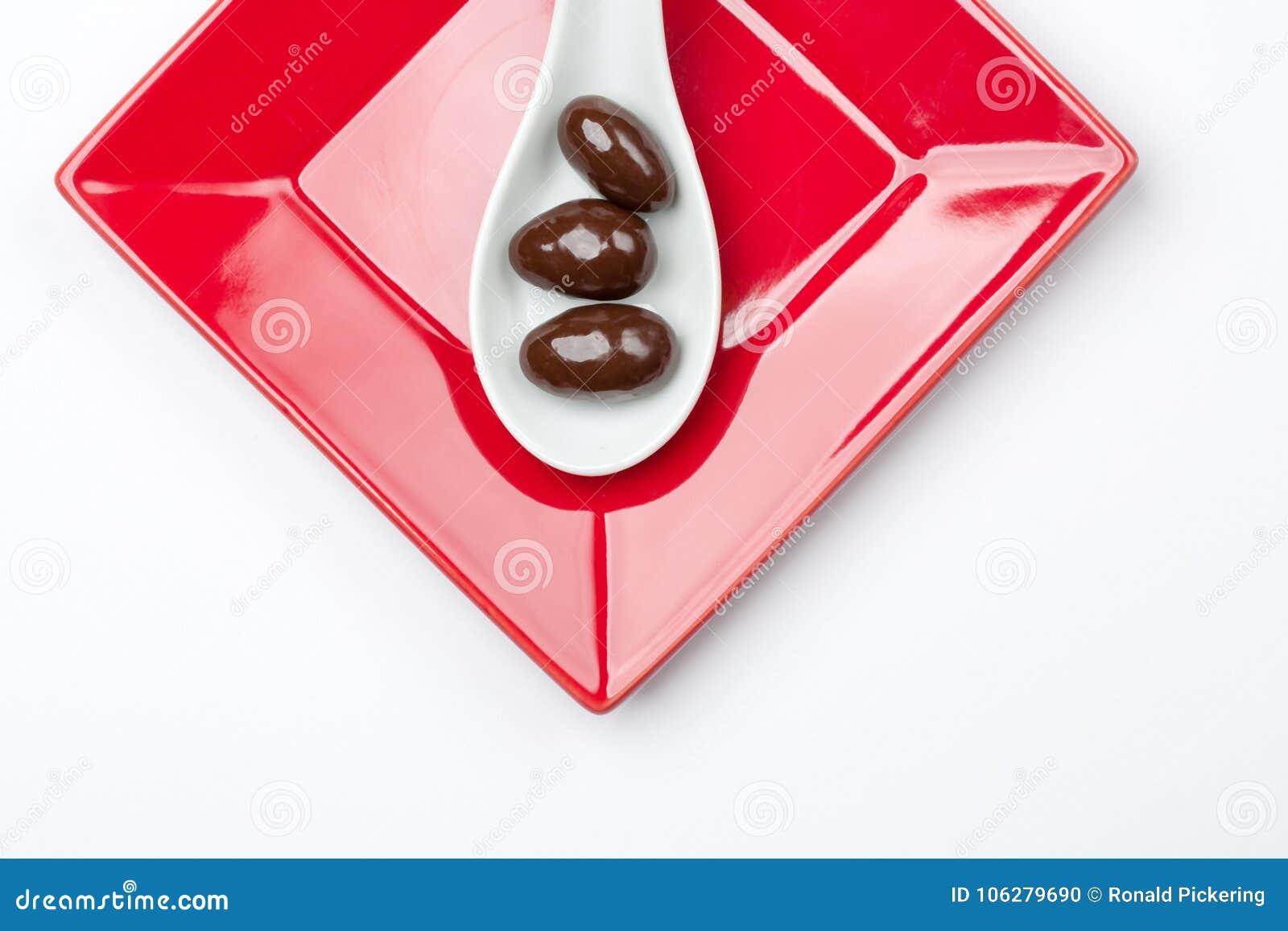 Καλυμμένα σοκολάτα αμύγδαλα στο άσπρο κουτάλι στο κόκκινο πιάτο