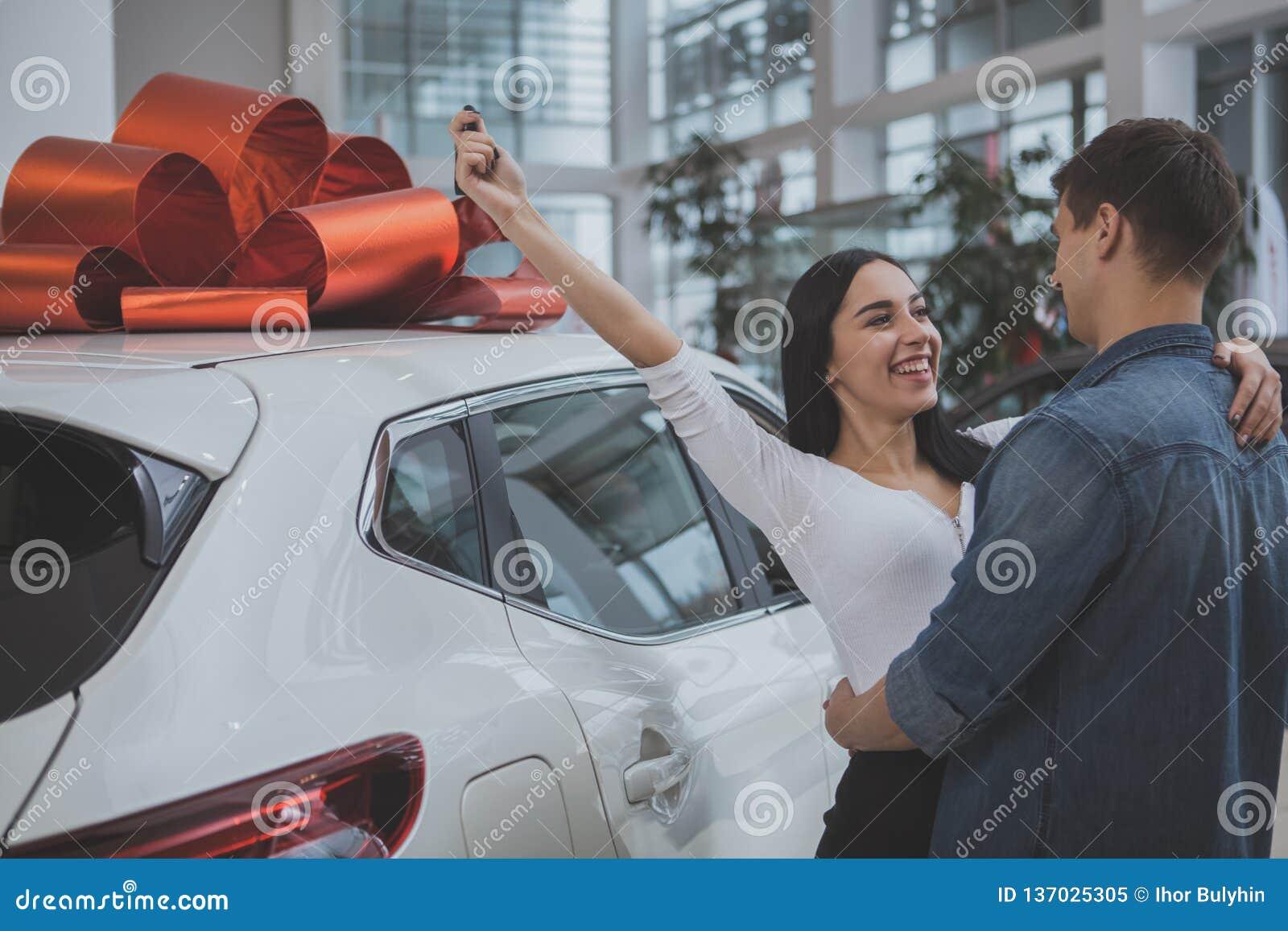 Καλό νέο παντρεμένο ζευγάρι που αγοράζει το νέο αυτοκίνητο από κοινού