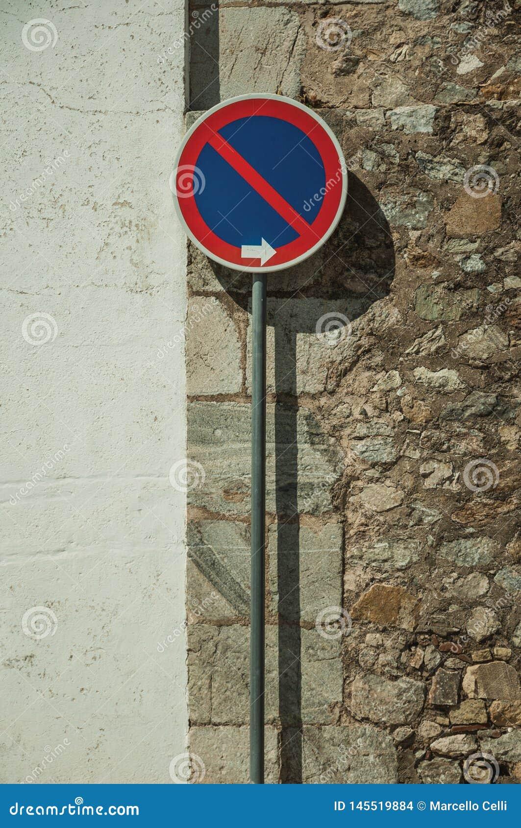 ΚΑΝΕΝΑ ΠΕΡΙΜΕΝΟΝΤΑΣ οδικό σημάδι μπροστά από τον τοίχο ασβεστοκονιάματος και πετρών σε Elvas