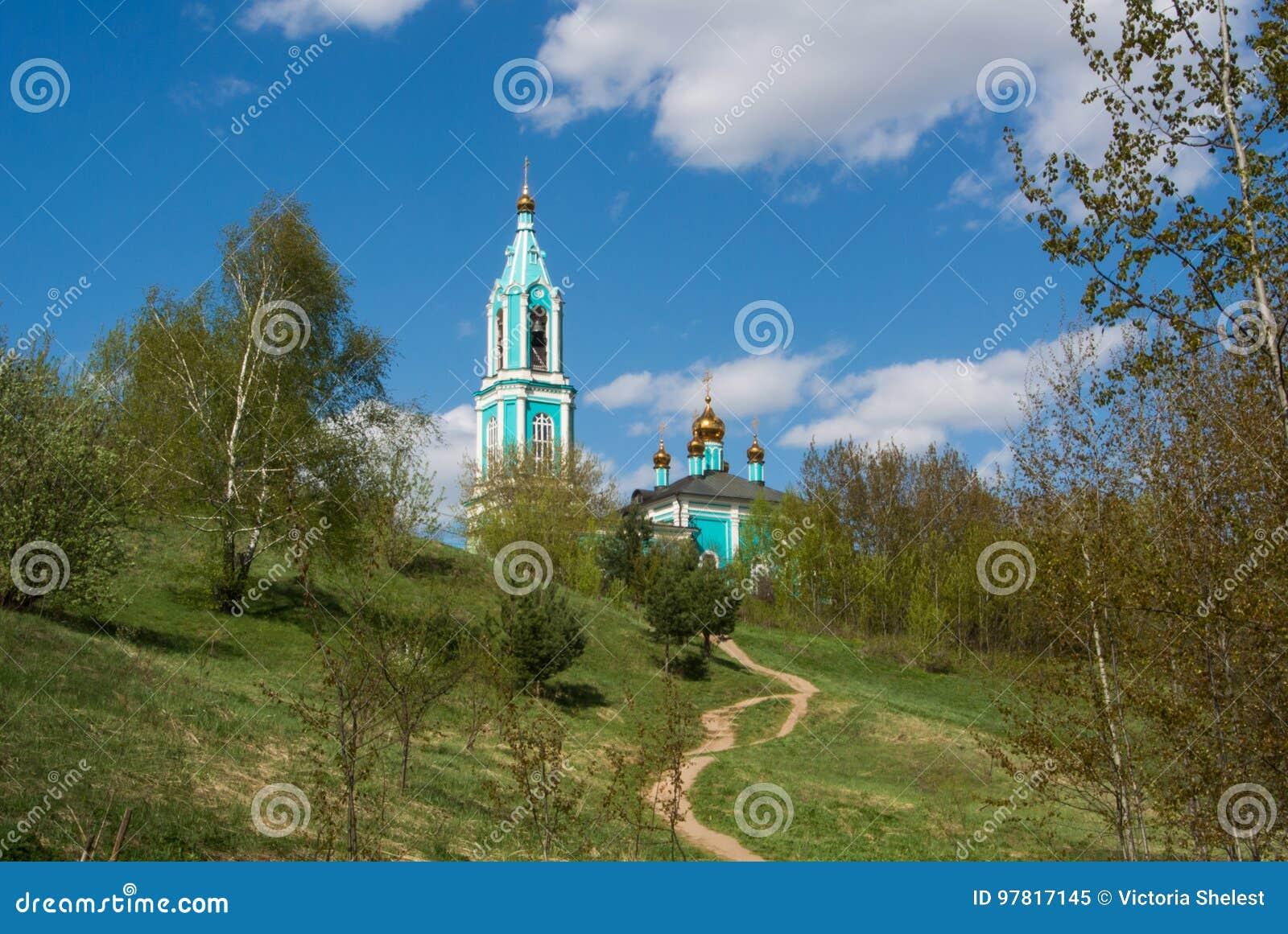 Κανονική άποψη της μικρής ρωσικής εκκλησίας ortodox πέρα από το λόφο, του όμορφου θερινού τοπίου με τα δέντρα και μιας πορείας