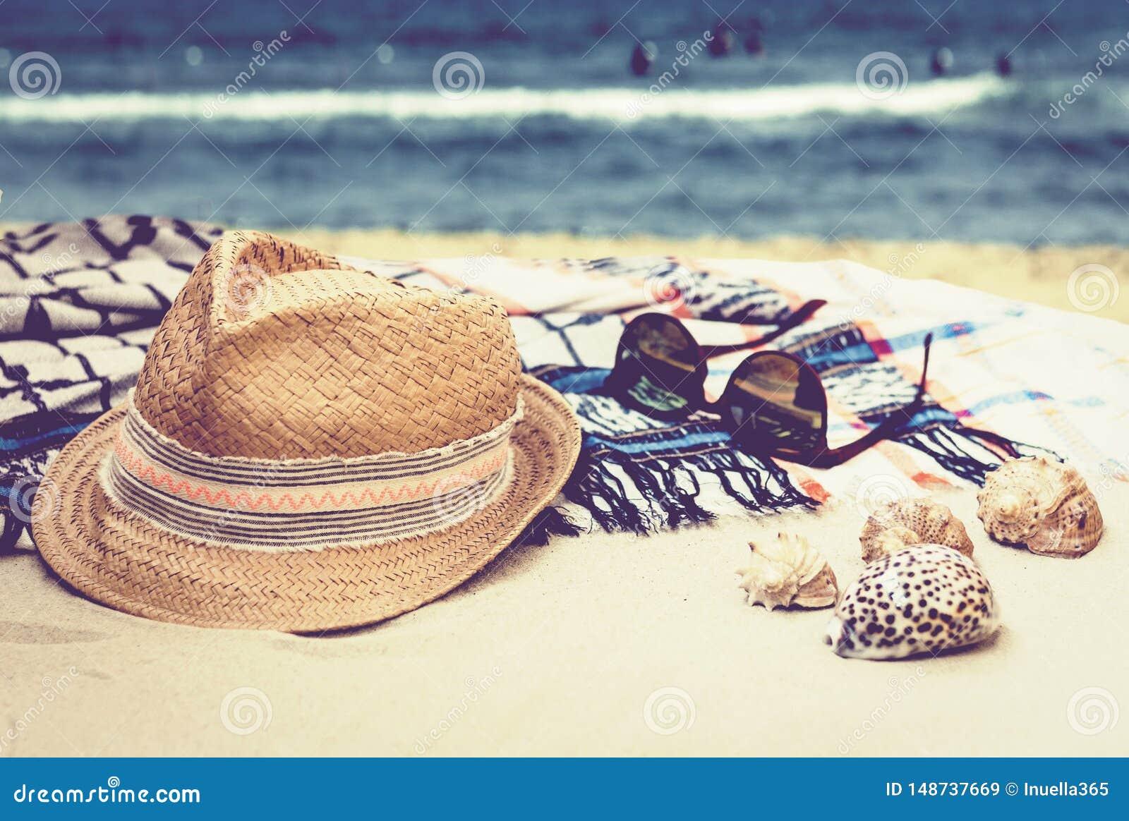 Καπέλο αχύρου, γυαλιά ήλιων και κάλυψη-επάνω στο beachwear περικάλυμμα σε μια τροπική παραλία με τα κοχύλια θάλασσας