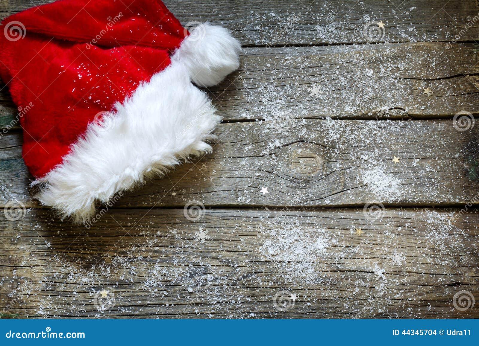 Καπέλο Άγιου Βασίλη στο εκλεκτής ποιότητας ξύλινο υπόβαθρο Χριστουγέννων πινάκων