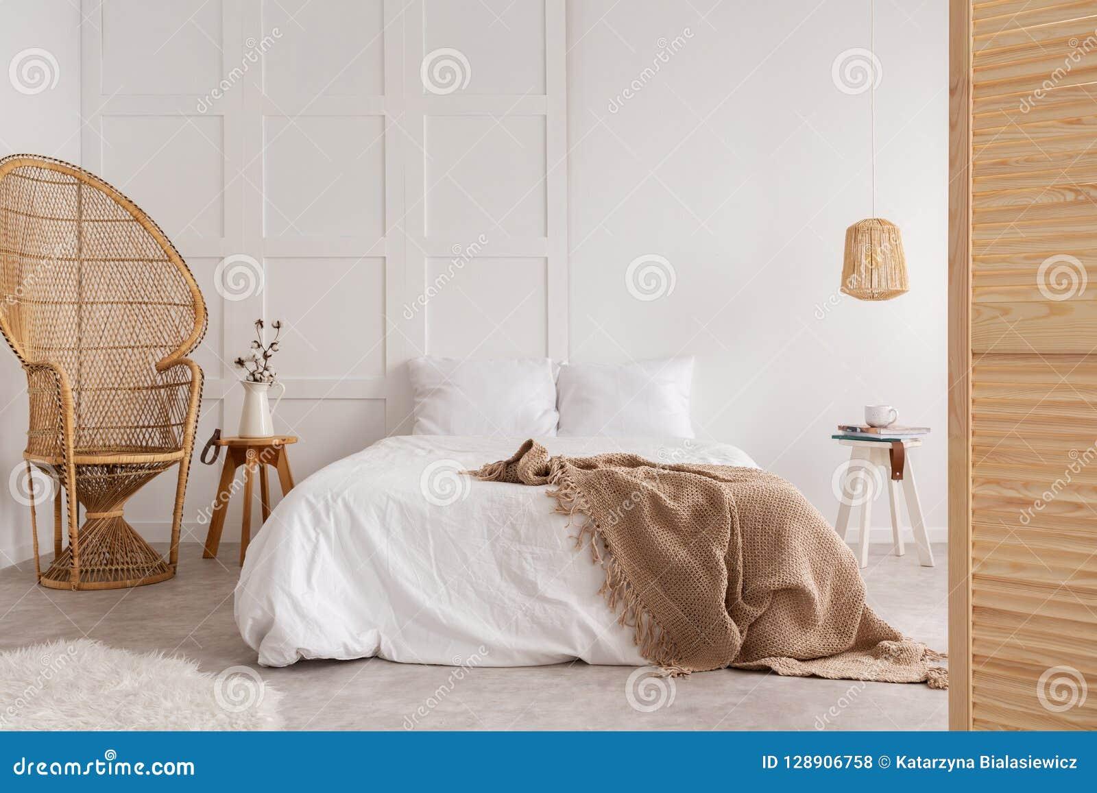 Καρέκλα ινδικού καλάμου και ξύλινος πίνακας δίπλα στο κρεβάτι με το καφετί κάλυμμα στο άσπρο εσωτερικό κρεβατοκάμαρων Πραγματική