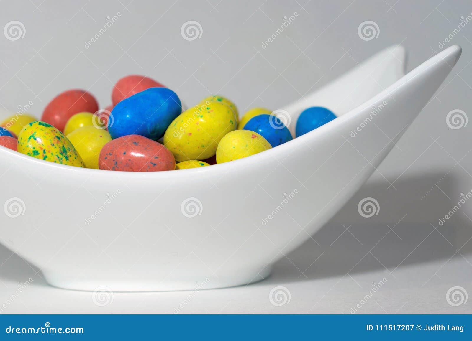 Καραμέλα αυγών Πάσχας στο άσπρο γλυπτό κύπελλο