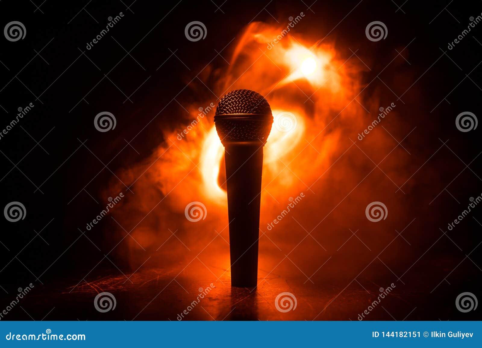Καραόκε μικροφώνων, συναυλία Φωνητικό ακουστικό mic στο χαμηλό φως με το θολωμένο υπόβαθρο Ζωντανή μουσική, ακουστικός εξοπλισμός