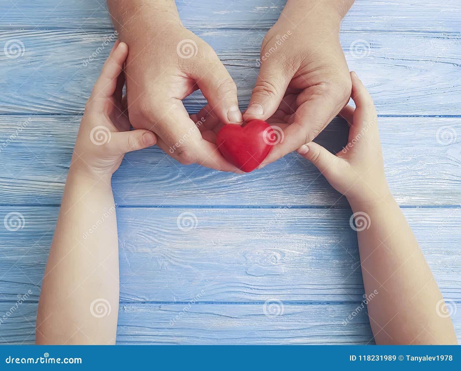 Καρδιά εκμετάλλευσης μπαμπάδων και παιδιών χεριών ημέρας πατέρων ` s σε ένα μπλε ξύλινο υπόβαθρο