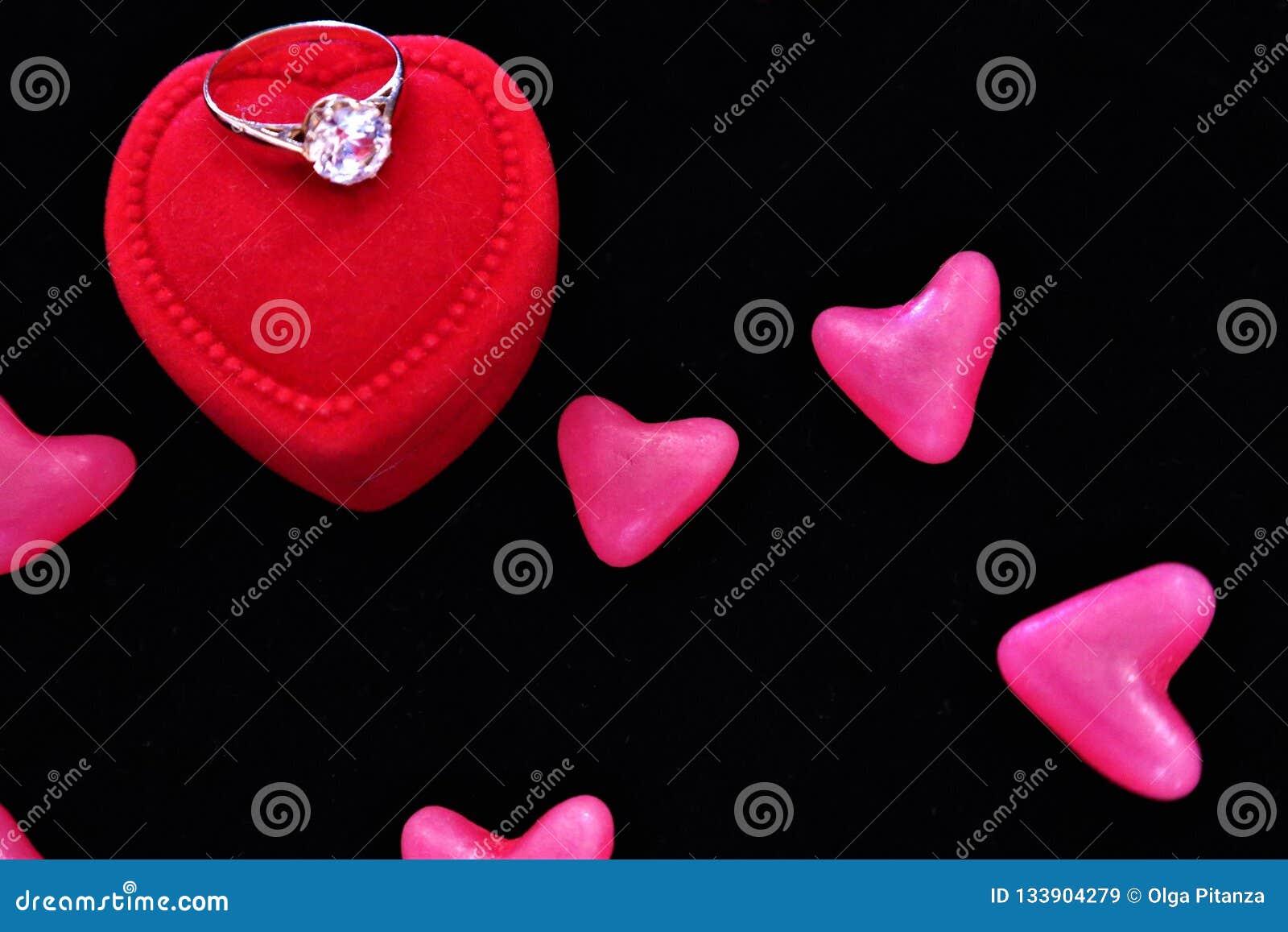 Καρδιές και ένα κόκκινο κιβώτιο με τα δαχτυλίδια βαλεντίνος ημέρας s
