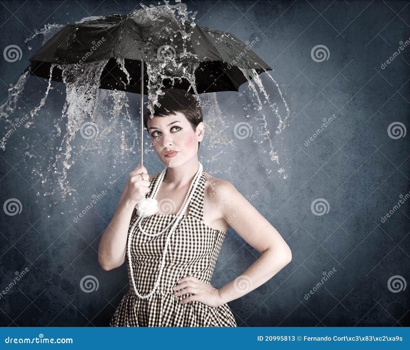 Καρφίτσα-επάνω στο κορίτσι με την ομπρέλα κάτω από τον παφλασμό ύδατος