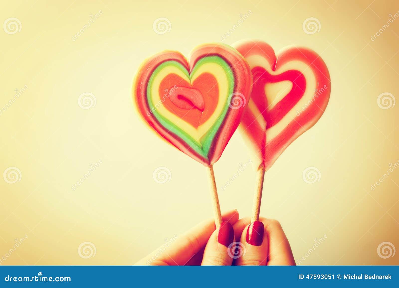 Καρδιά που διαμορφώνεται ζωηρόχρωμη lollipops στο χέρι γυναικών