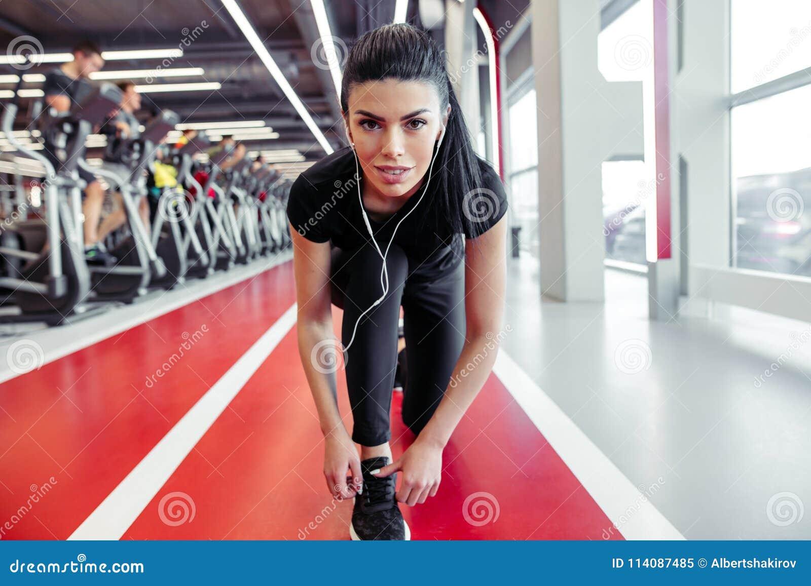 Κατάλληλο κορίτσι για να κάνει κάτω τα κορδόνια στη γυμναστική ικανότητας πρίν τρέχει την άσκηση workout