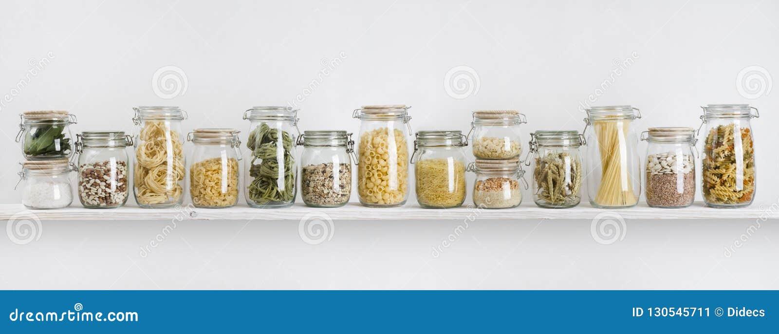 Κατάταξη των άψητων παντοπωλείων στα βάζα γυαλιού που τακτοποιούνται στο ράφι