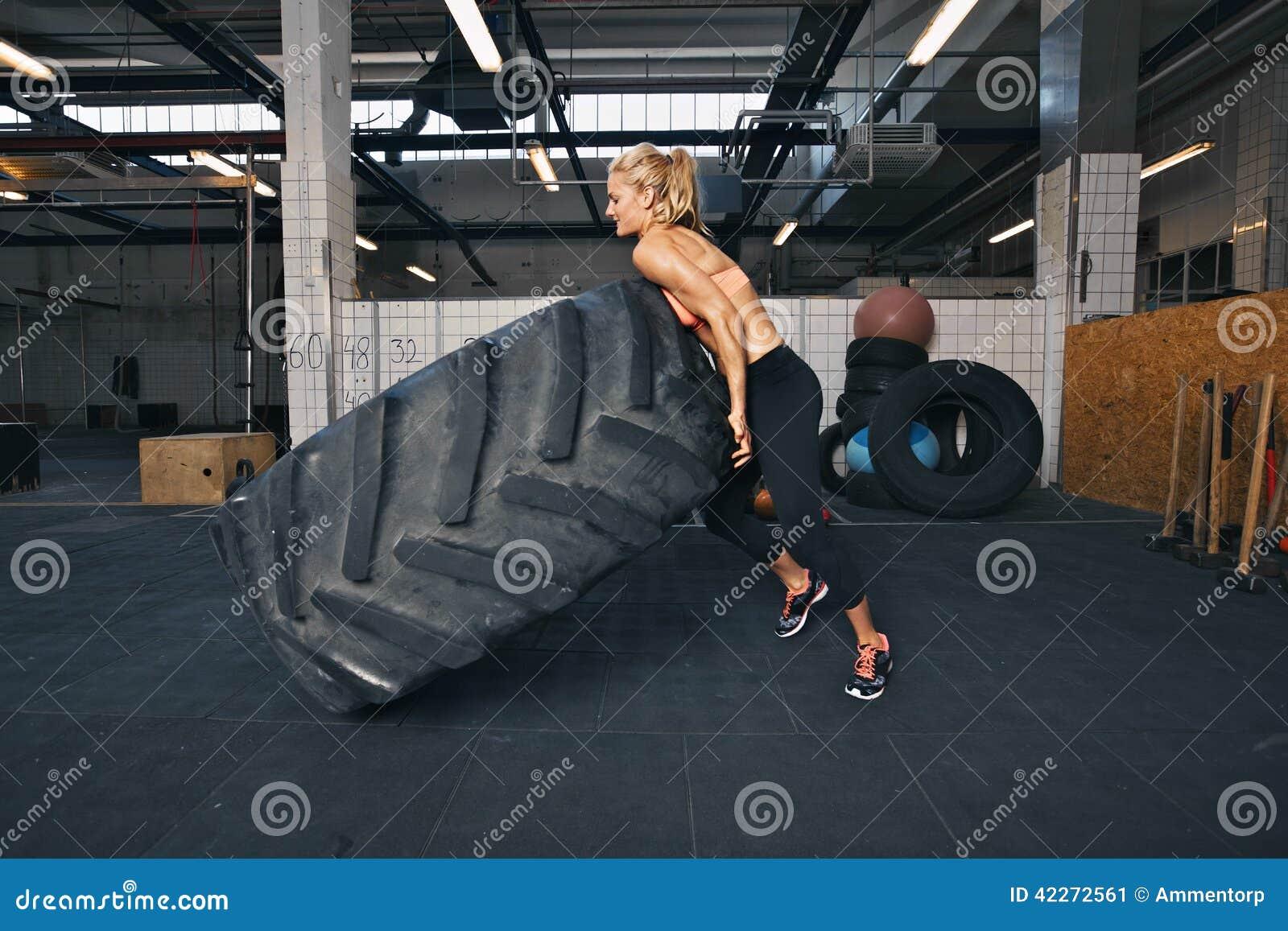 Κατάλληλος θηλυκός αθλητής που κτυπά μια τεράστια ρόδα