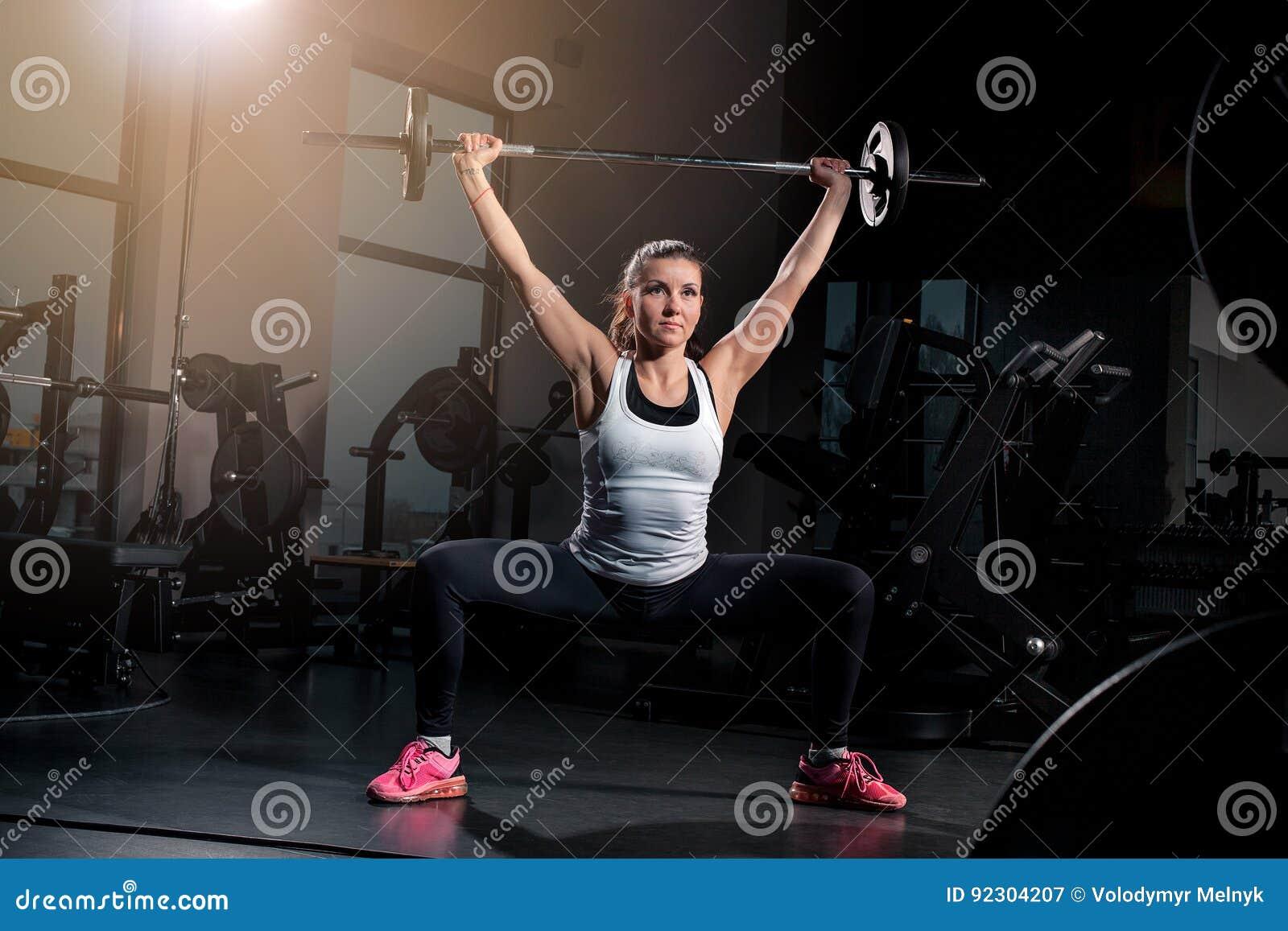Κατάλληλο νέο να φανεί ανύψωσης γυναικών barbells, επιλύοντας σε μια γυμναστική